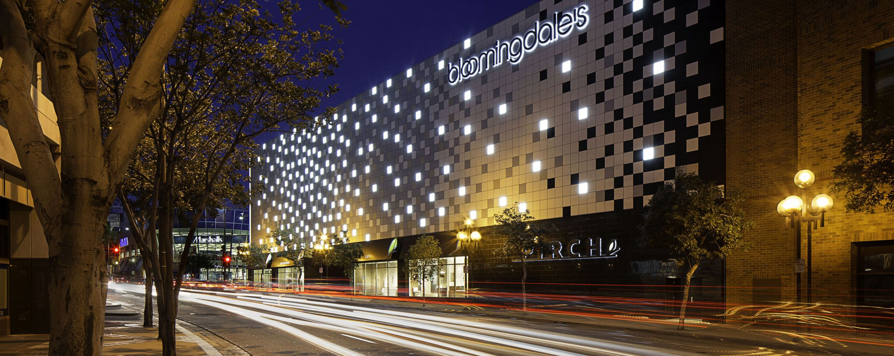 At night, a GGP property Bloomingdales is lit up welcoming shoppers as cars pass by.