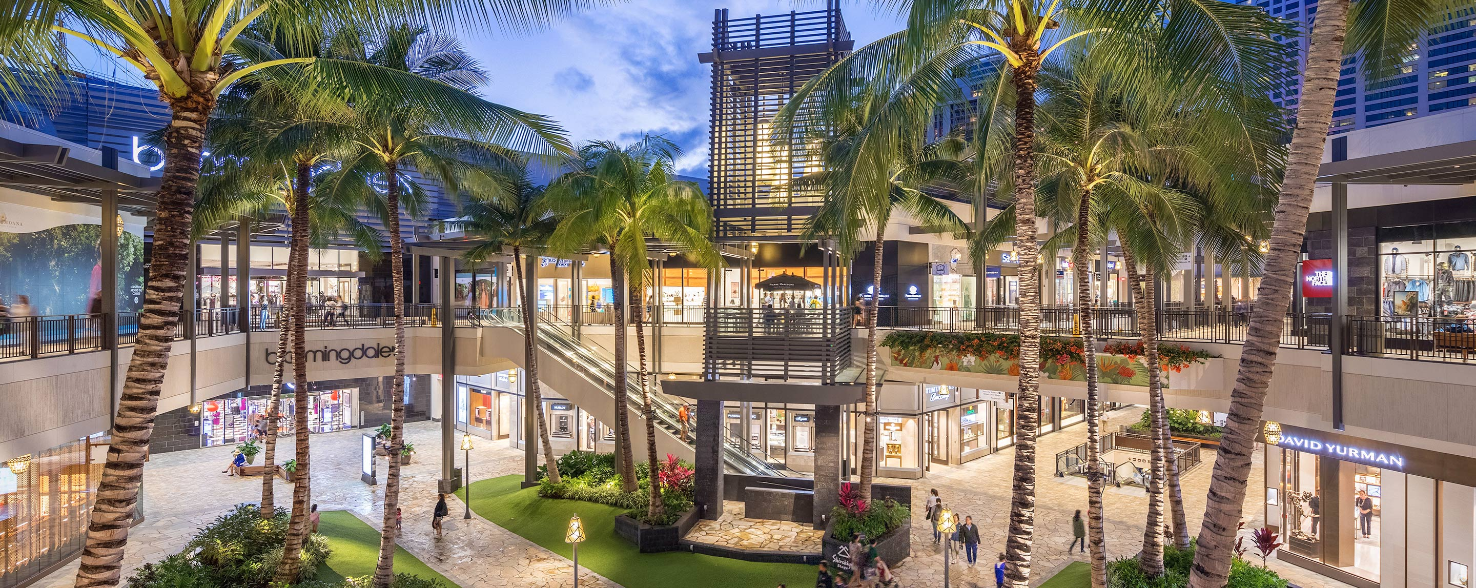 At dusk, the exterior of Ala Moana Center lights up with palm trees just outside the building.