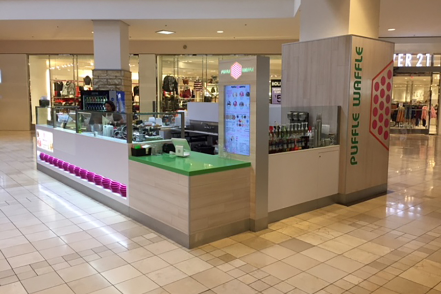 A Puffle Waffle kiosk at the center of a mall with green countertops and a pink logo of a waffle.