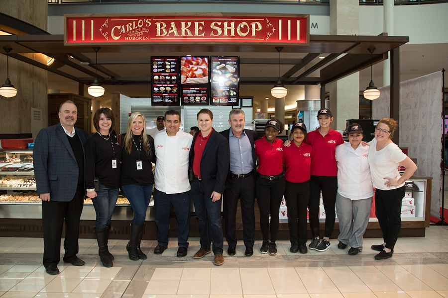 The staff at Carlo's Bake Shop stands together in front of their bakery kiosk, some in uniforms and others in business casual.