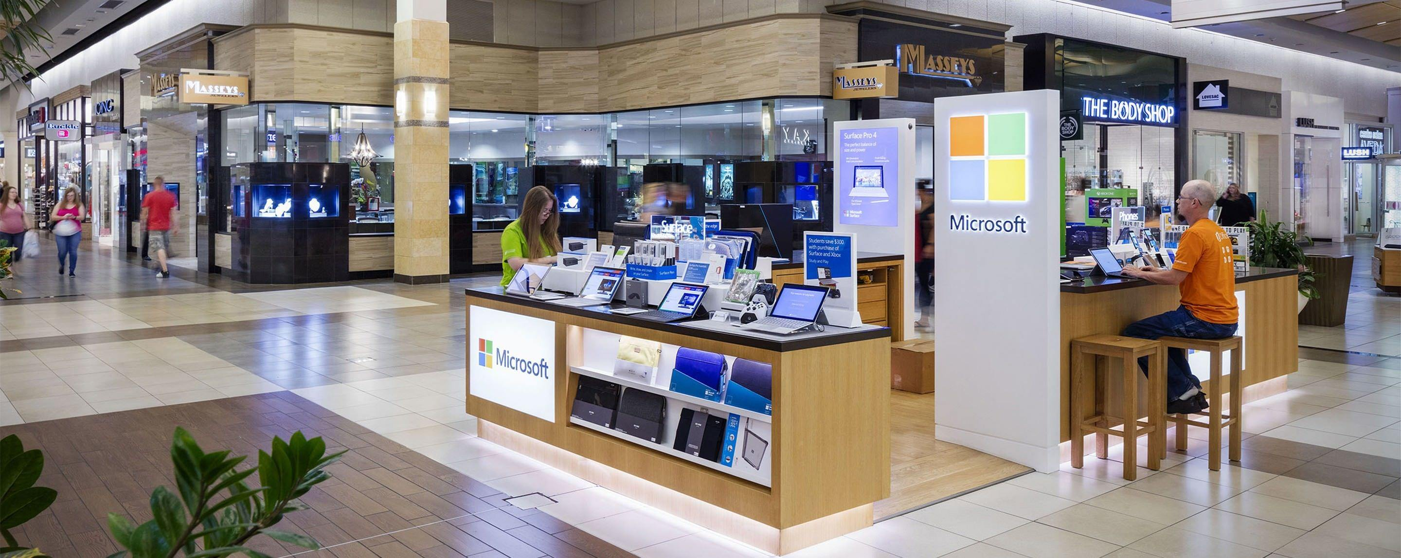 In a GGP property common area, a Microsoft pop up is displayed with shoppers working with the products.