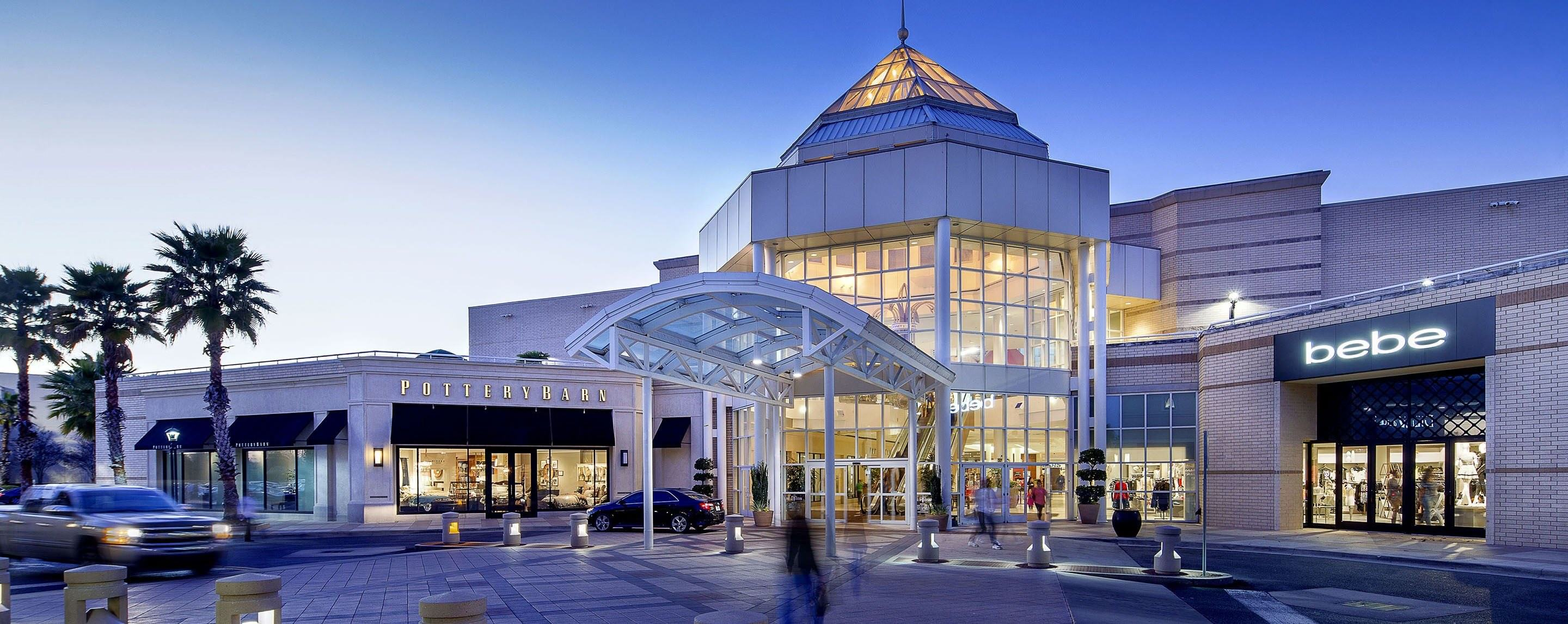 A GGP property entrance is lit up with their glass atrium with Pottery Barn and bebe stores directly to the sides.