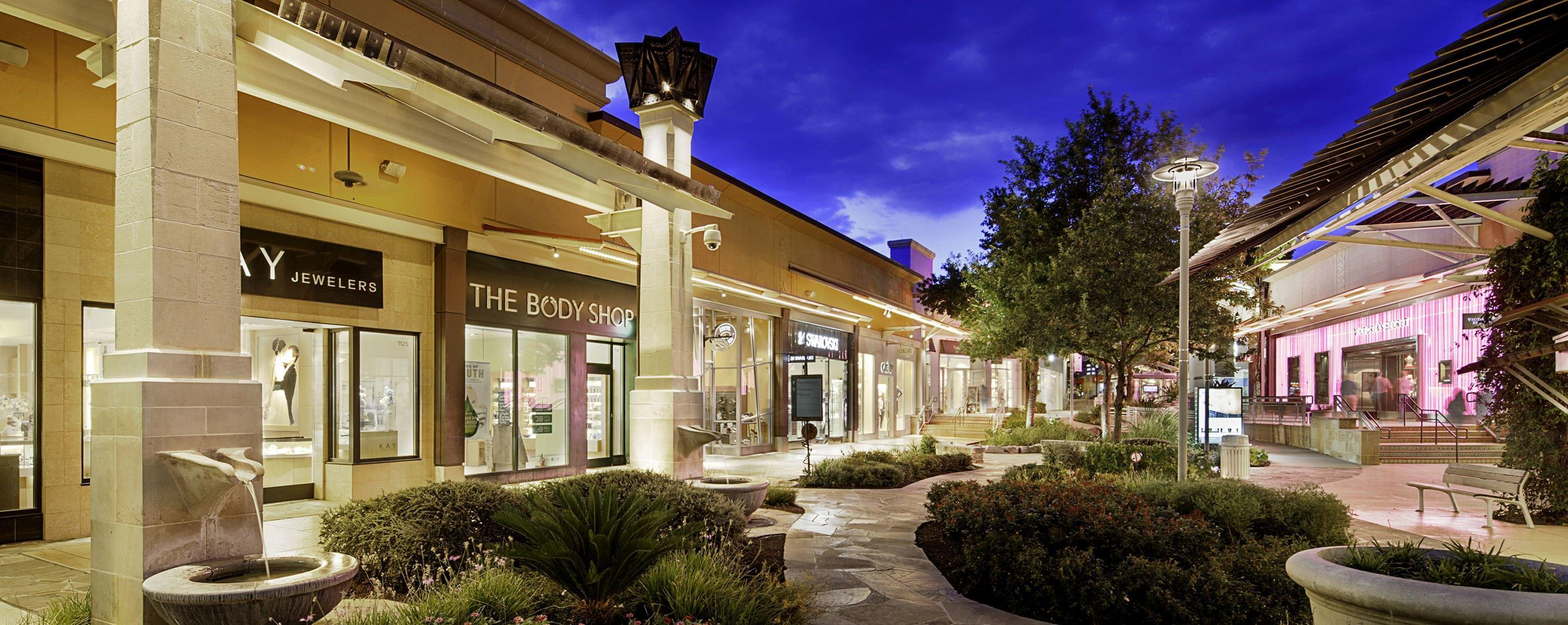 At night, a GGP property outdoor walkway has store fronts brightly lit with decorated with trees and plants.