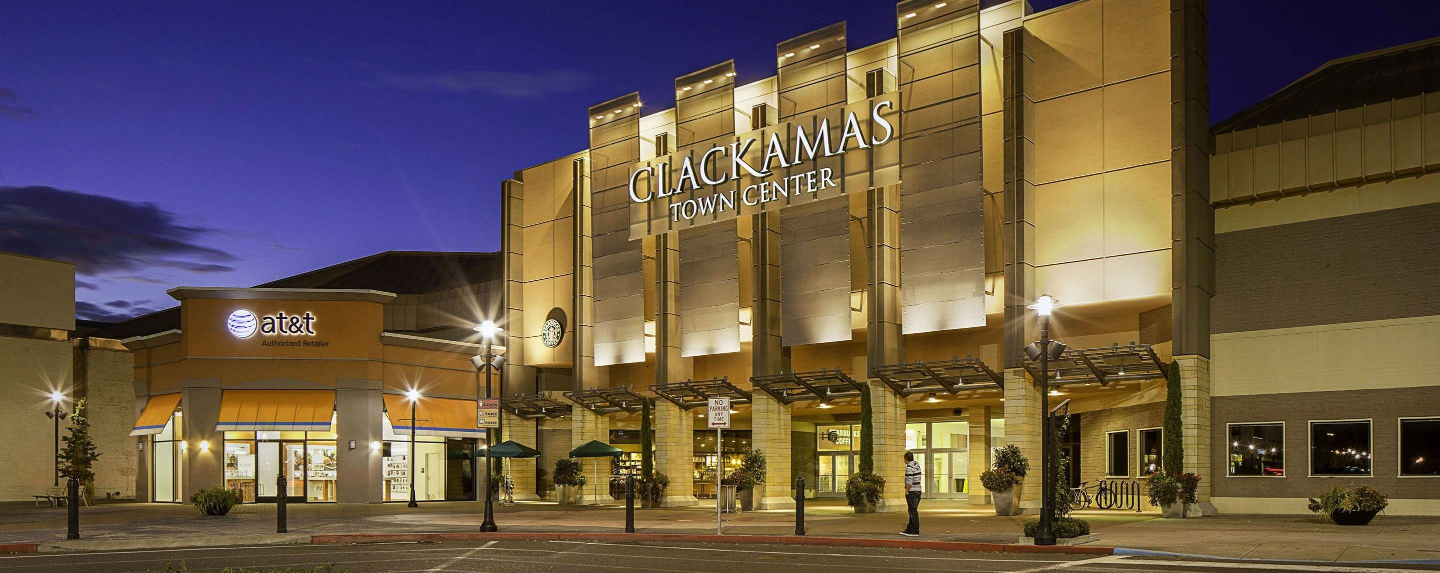 At night, the Clackamas Town Center sign is brightly shining on the building's main entrance with potted plants as décor.