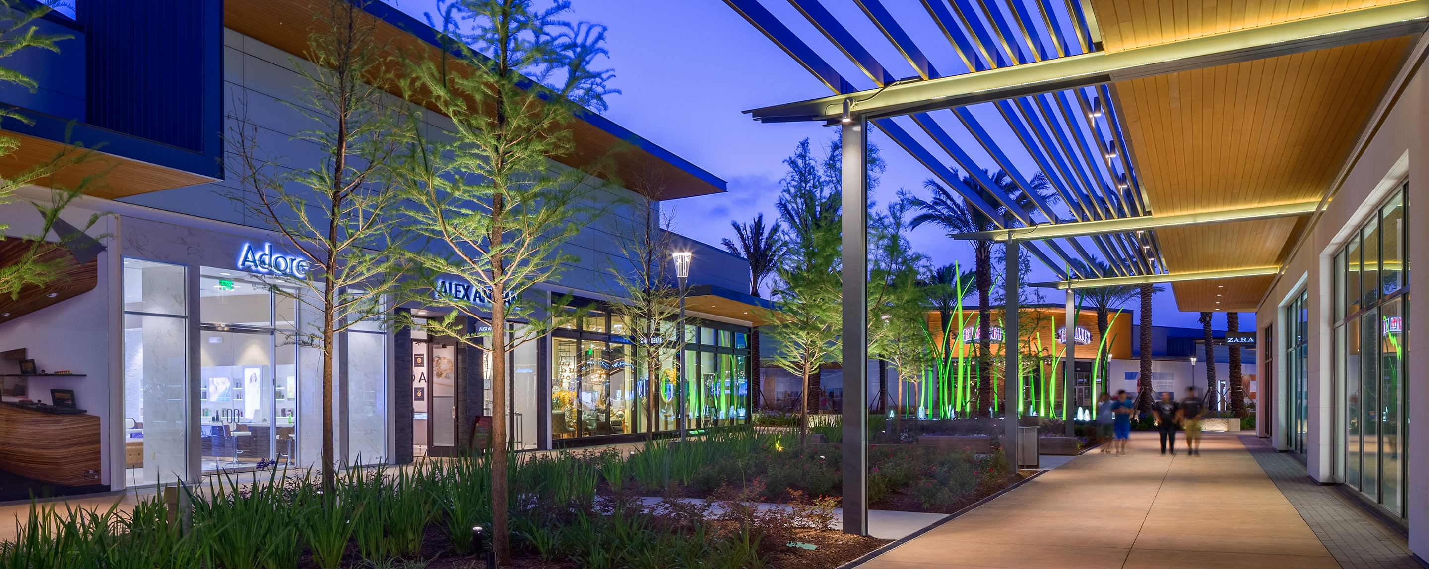 One of the well-lit outdoor walkways at Baybrook mall allows shoppers to view storefronts, trees and greenery in the evening.