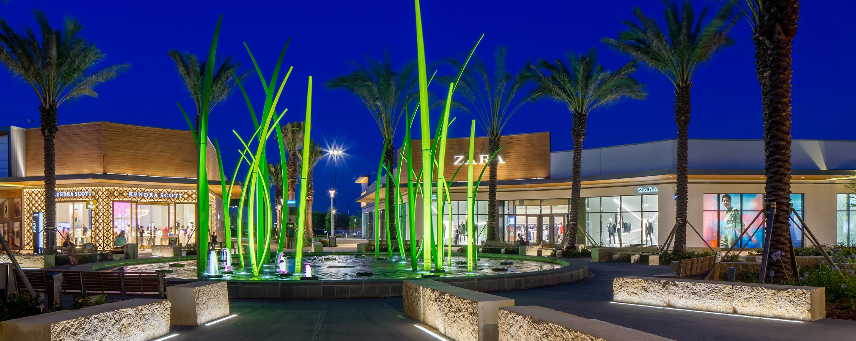 An outside common area at night is light up by a running fountain with benches and resting areas for shoppers.
