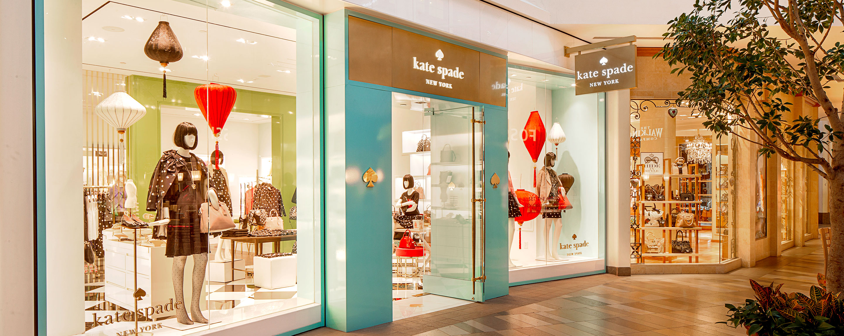 In a Beachwood Place interior walkway, storefronts including Kate Spade are lit up for shoppers.