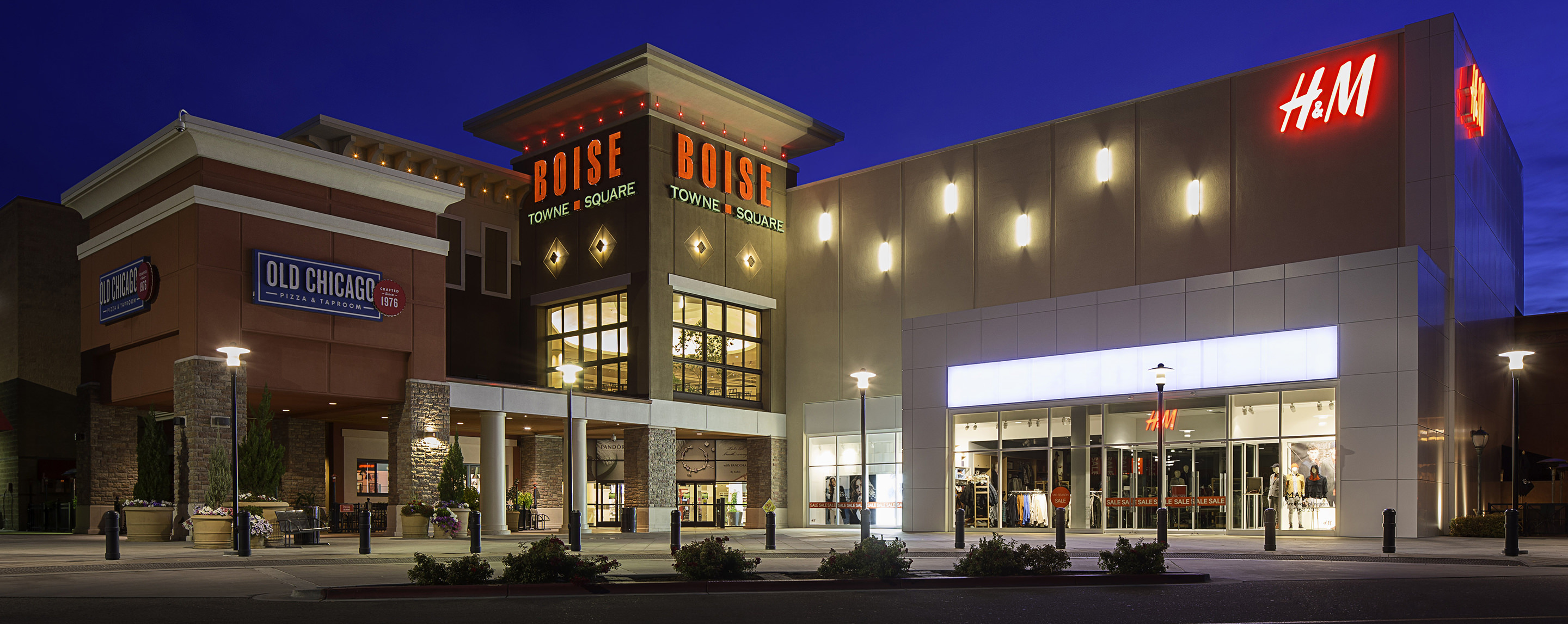 Outside Boise Town Square at night, the property is lit up showcasing H&M and a mall entrance decorated with greenery.