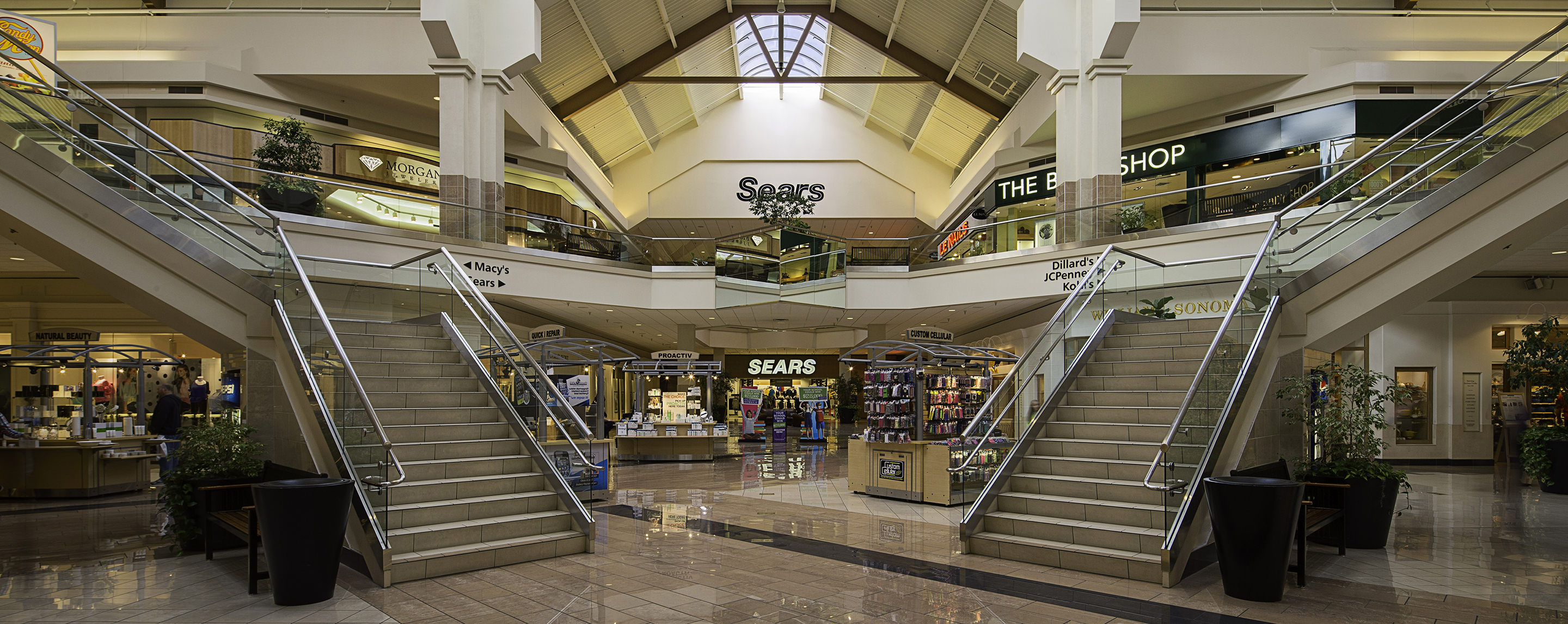 In a Boise Town Square atrium and common area, you see staircases, benches, kiosks, and store fronts.
