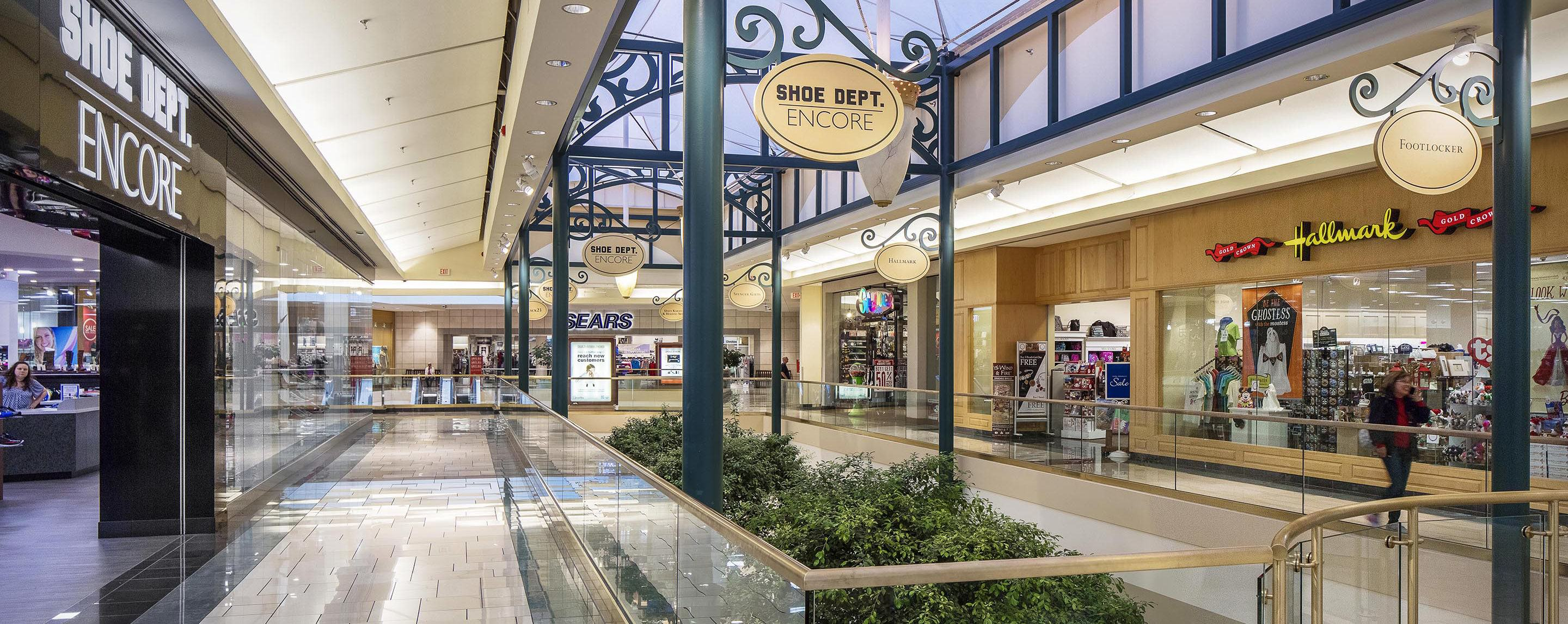 A second floor walkway at the Shoppes at Buckland Hills are lined with store fronts with an open area to look into the trees below.