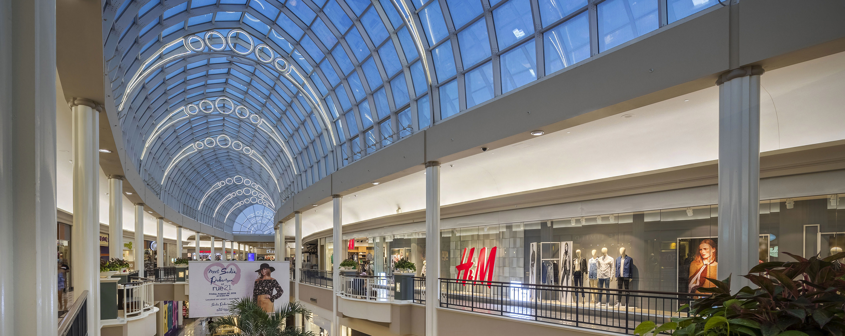 Inside the upstairs of the Carolina Place mall, store fronts show trendy clothing as the sun shines through the class interior roof.