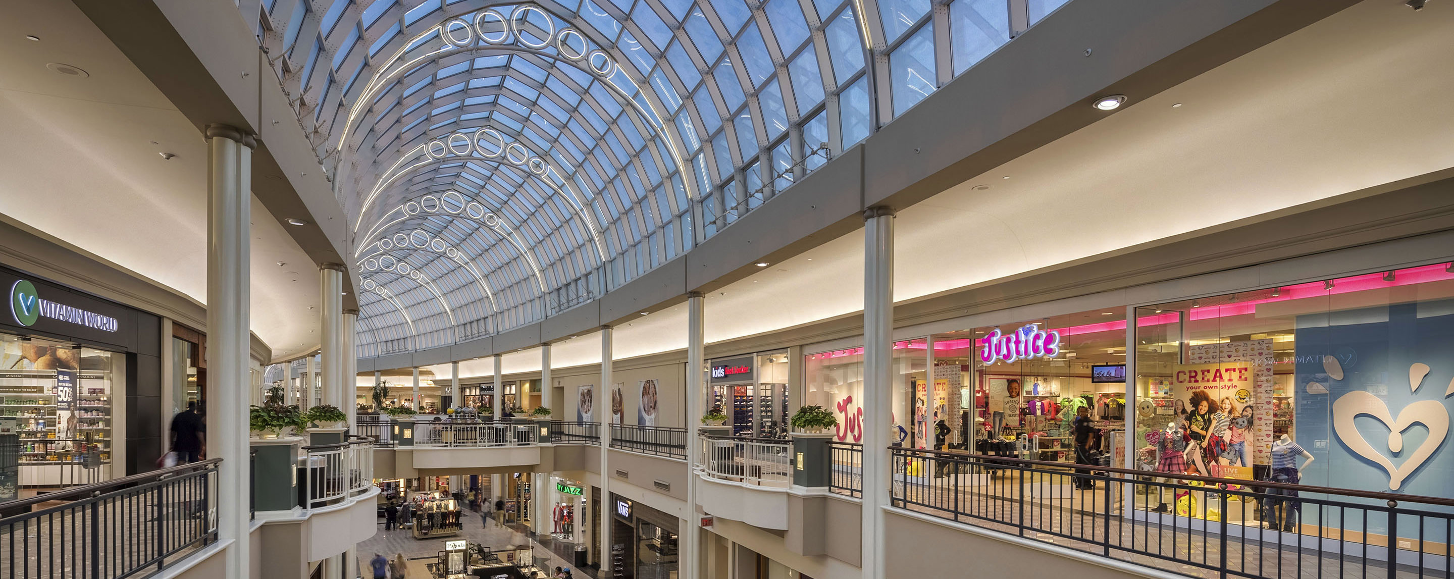 Upstairs inside the Carolina Place mall, store fronts display products and the sun is shining through the glass roof.