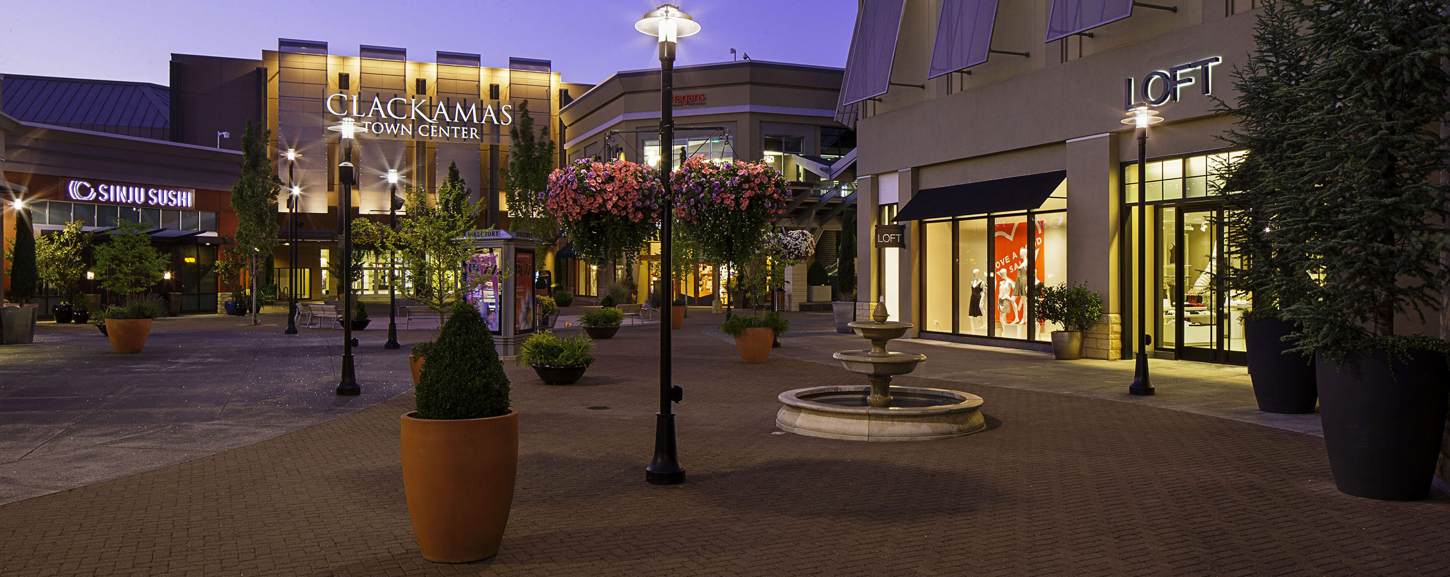 Outside at night, the common area leading into Clackamas Town Center is filled with fountains, flowers, potted plants, and light posts.