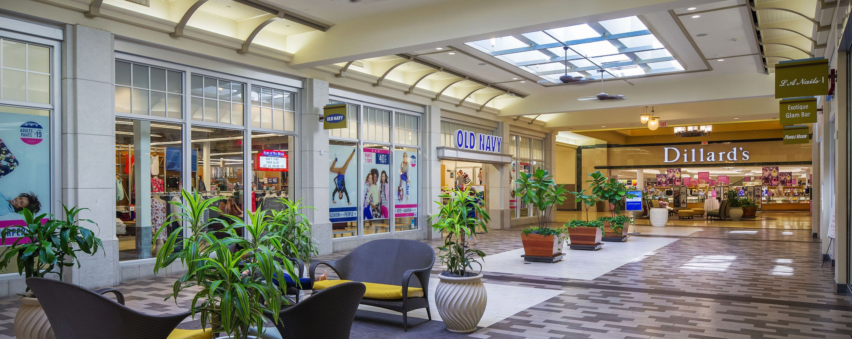 An interior common area of Coastland Center has seating options for shoppers and decorated with potted plants.