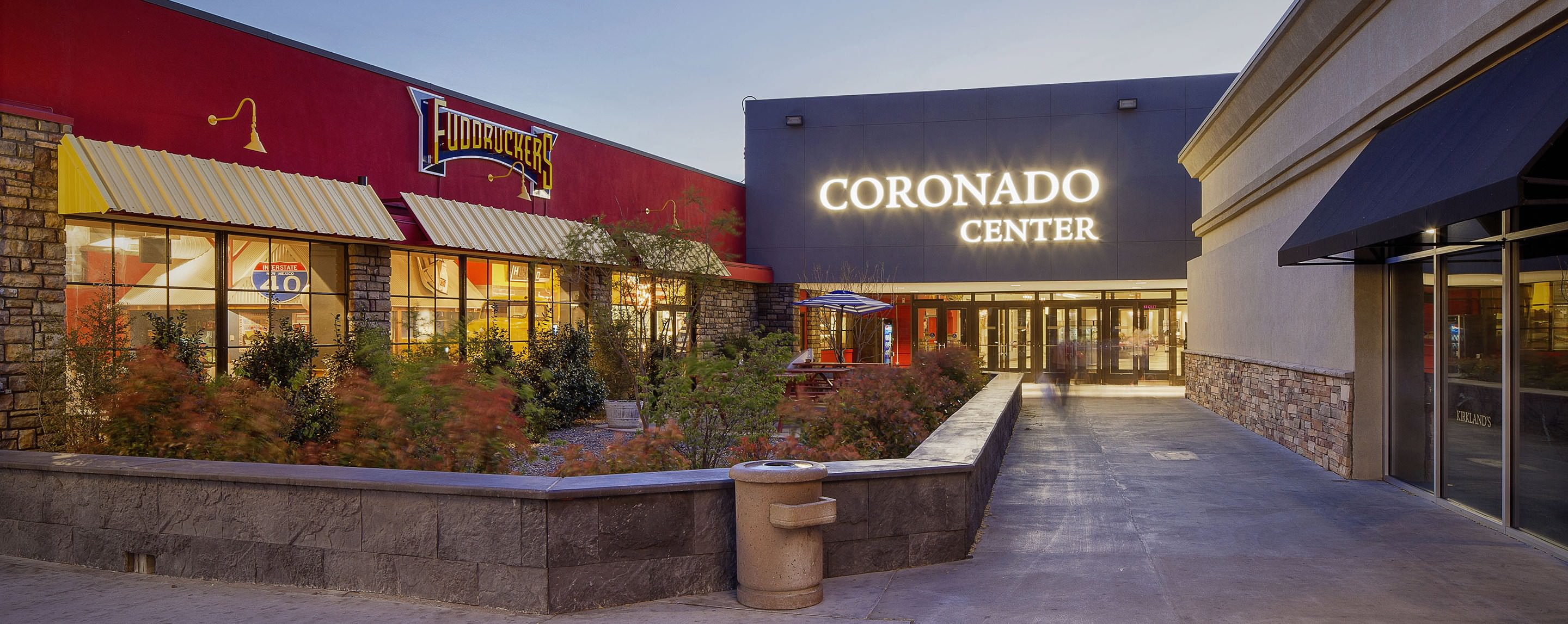 During the day, the Coronado Center entrance welcomes shoppers with plants, a seating area, and Fuddruckers.
