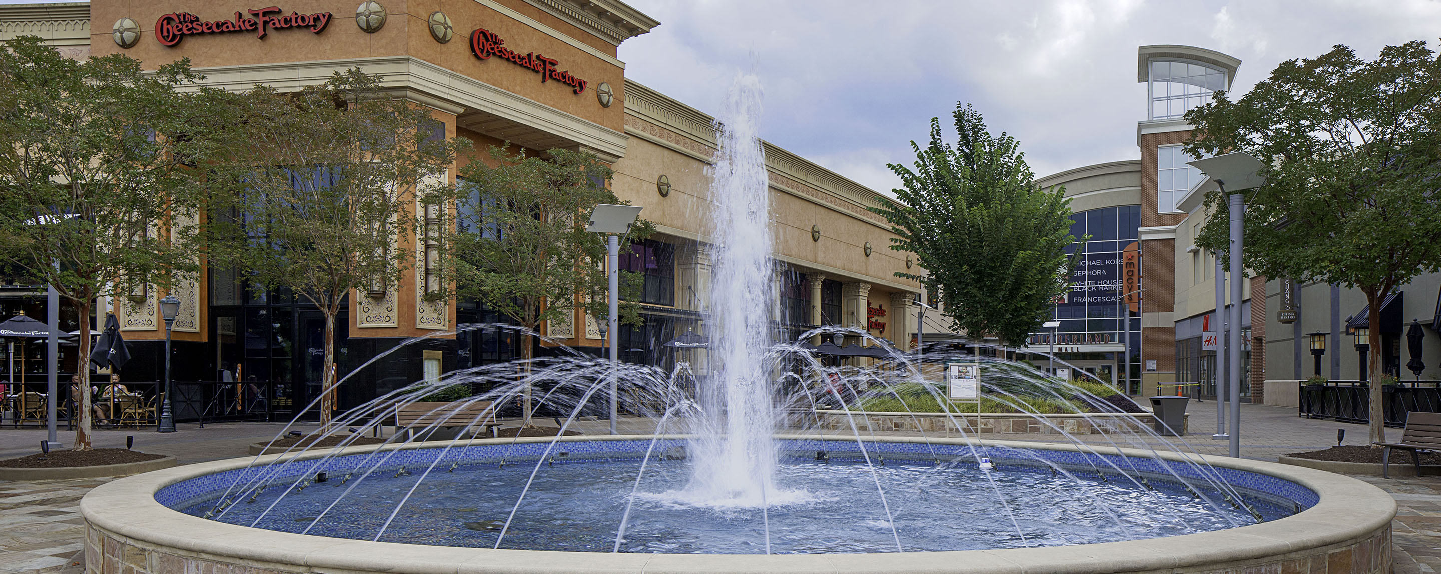A large fountain is in the common entrance area of Cumberland Mall along with dining options and benches for seating.