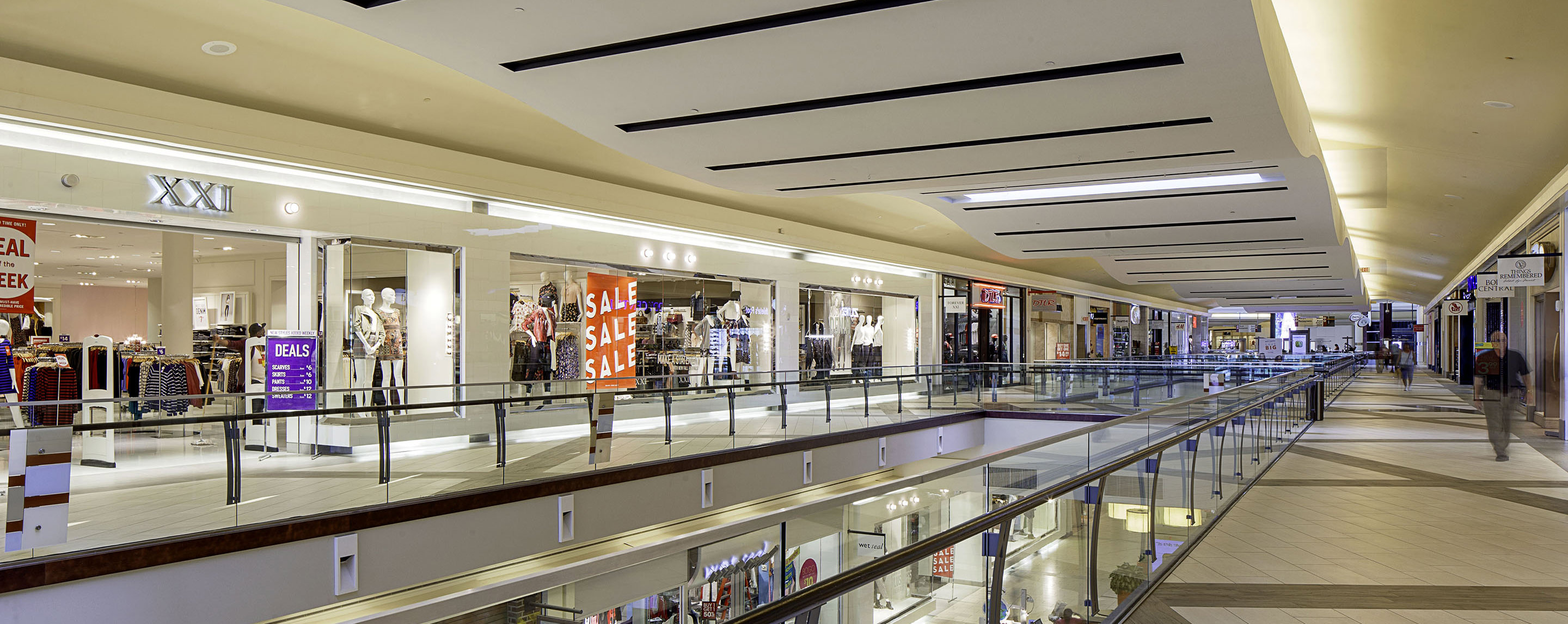 An upstairs walking inside Cumberland Mall is lined with store fronts, shoppers walking in hallways, and an opening to look at the floor below.