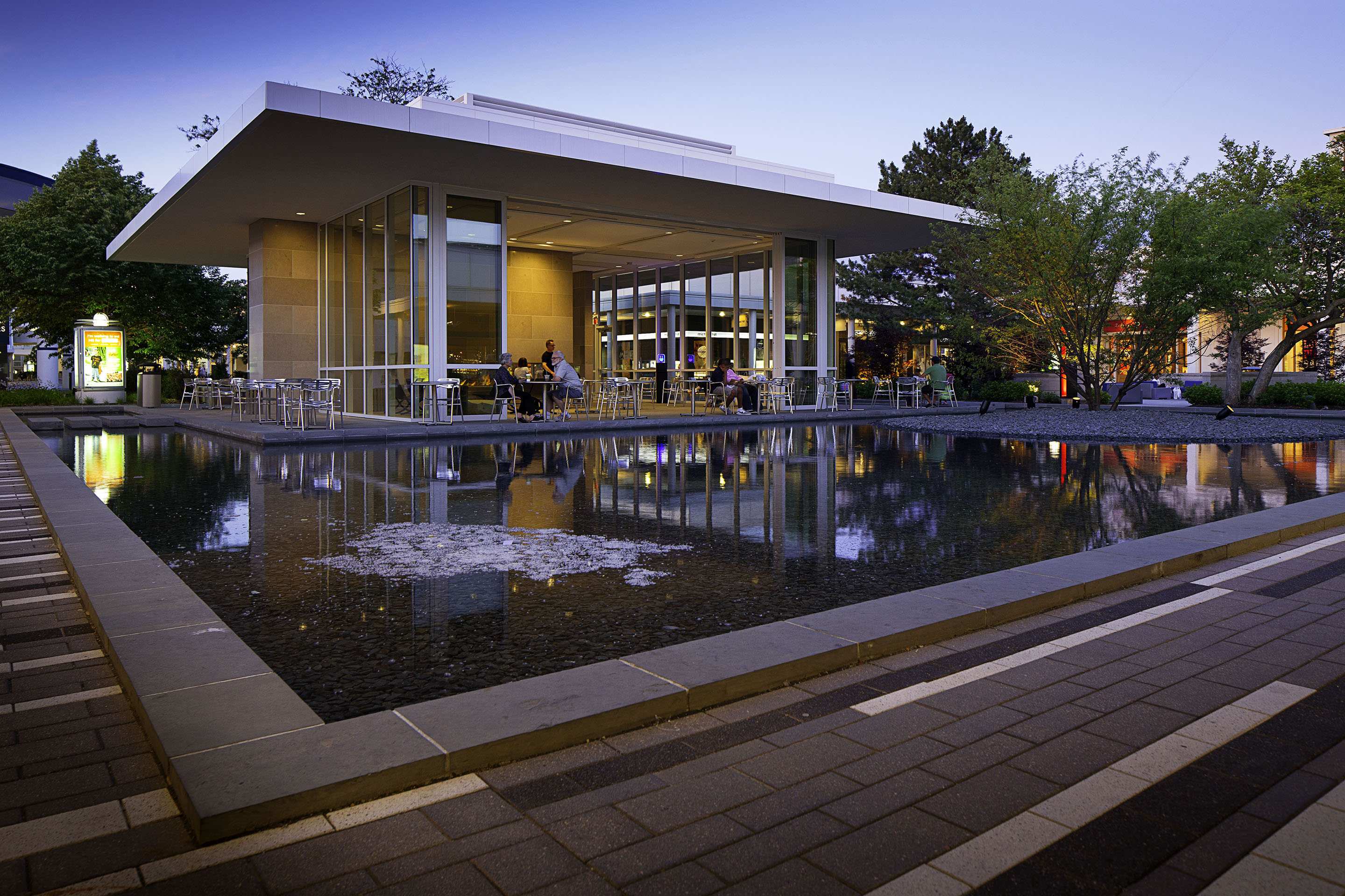 An outdoor seating area surrounded by a decorative pond is a popular spot for visitors at Oakbrook Center