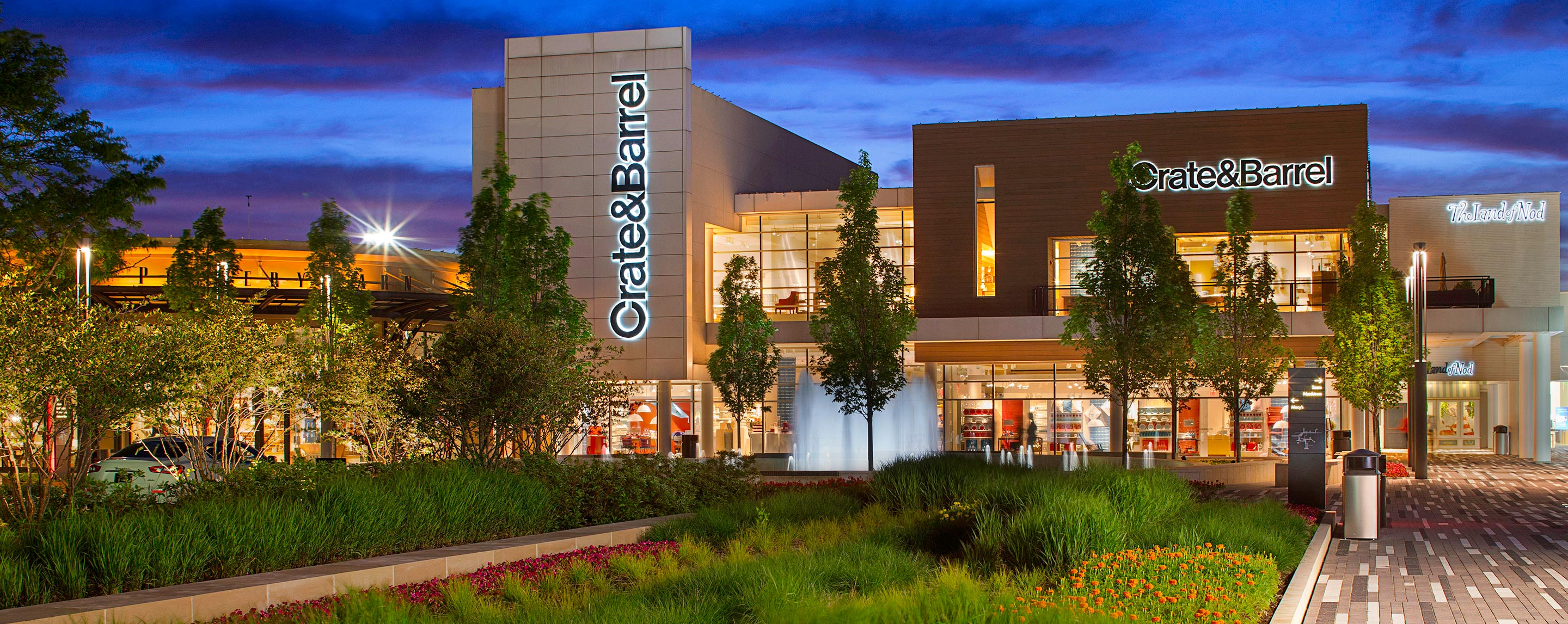 At dusk, GGP's Oakbrook Center has beautiful plants and trees in the common area in front of a Crate and Barrel store.