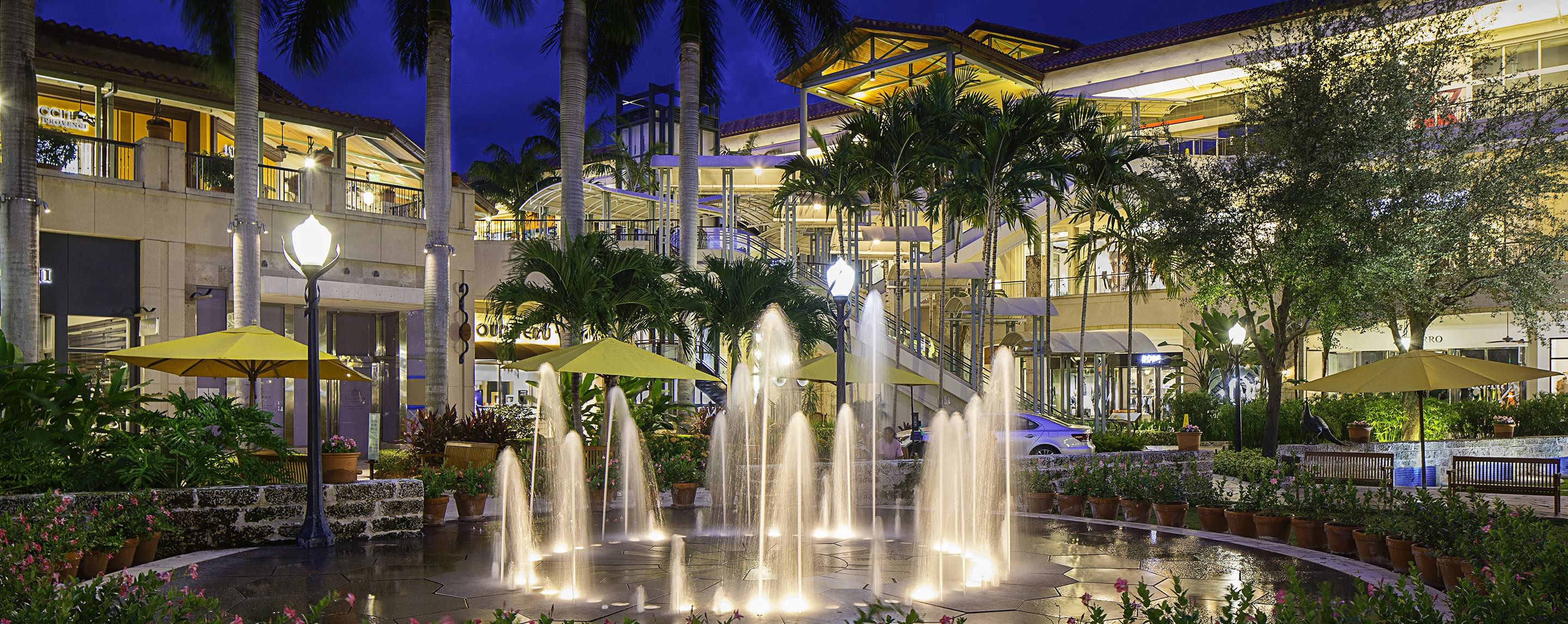 At night, a GGP property is beautifully lit up in a store front lined outdoor walkway decorated with fountains and trees.
