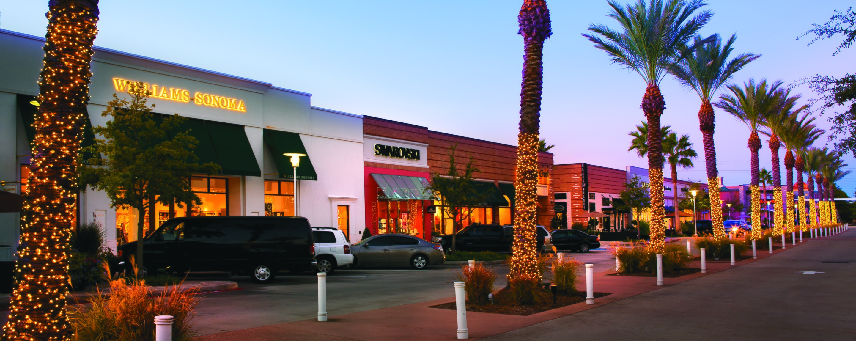 Outside the First Colony Mall, the streets and parking areas are lined with lit up palm trees and store fronts.