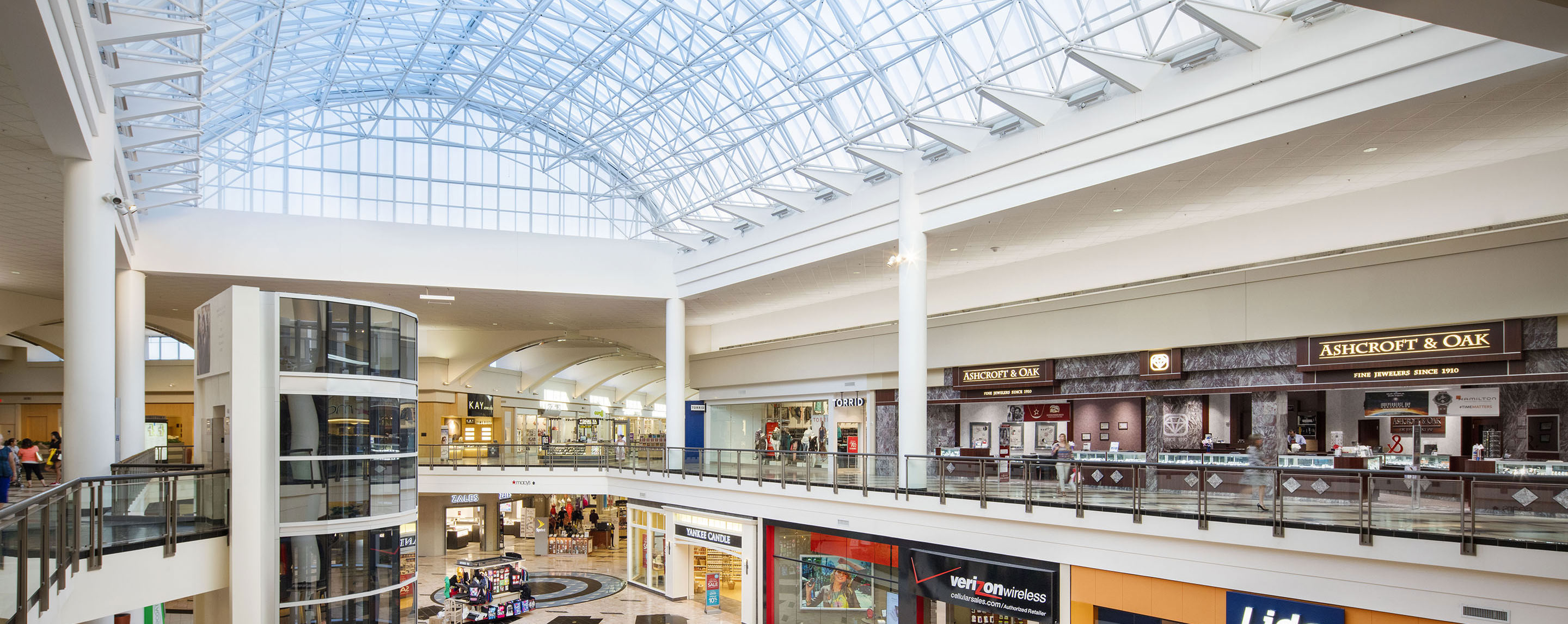 In the interior Florence Mall atrium, the glass ceiling allows the sun to shine on store fronts and kiosks on the first level.