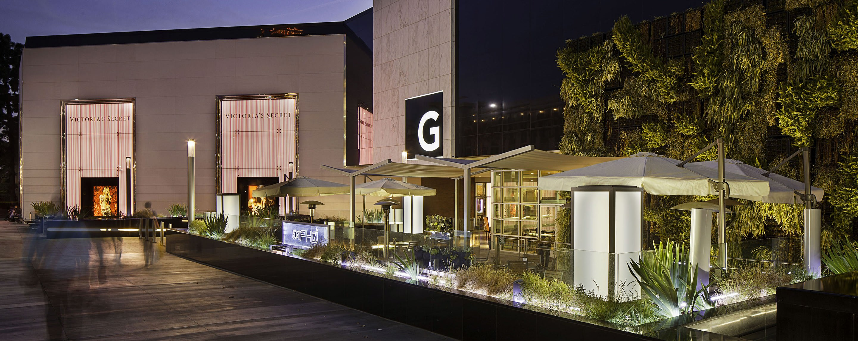At dusk, shoppers walk past a living wall, lush landscape and outdoor seating at the entrance of Glendale Galleria.
