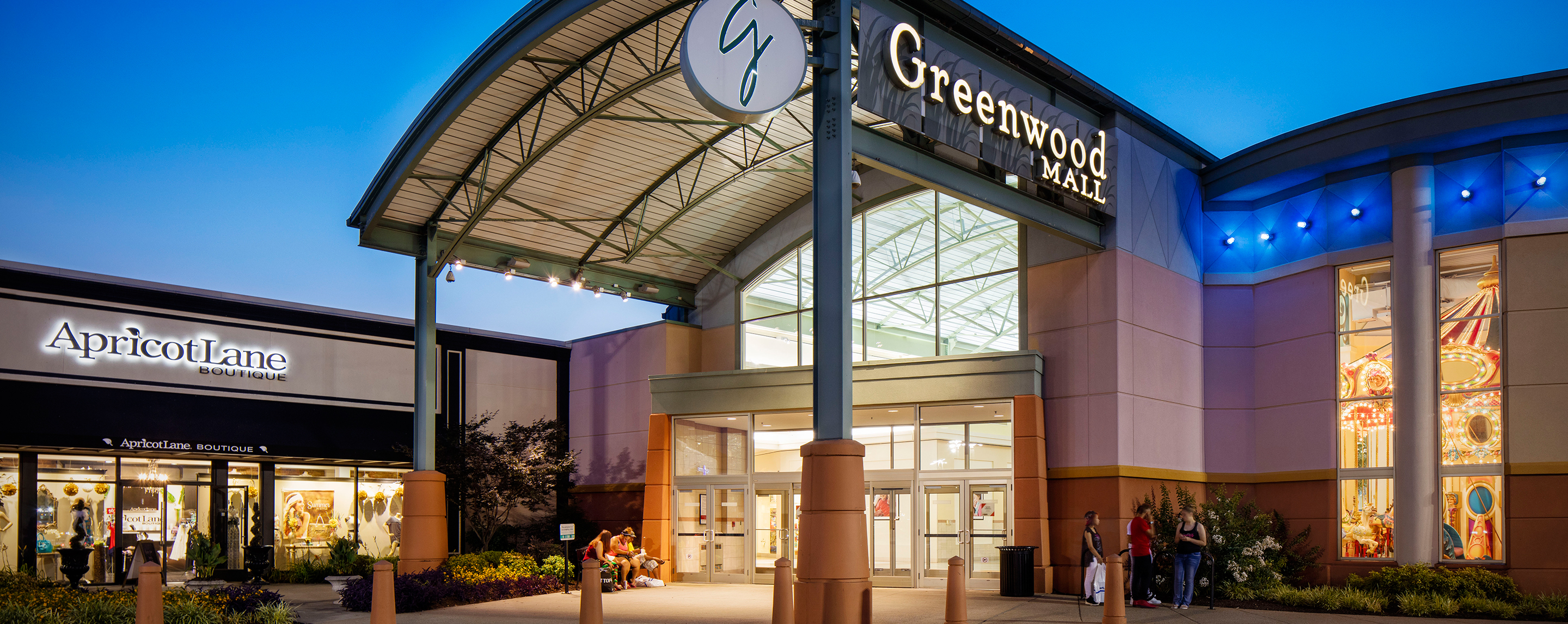 At night the exterior entrance of the Greenwood Mall is bright and welcoming as shoppers sit on benches to rest or meet up with friends.