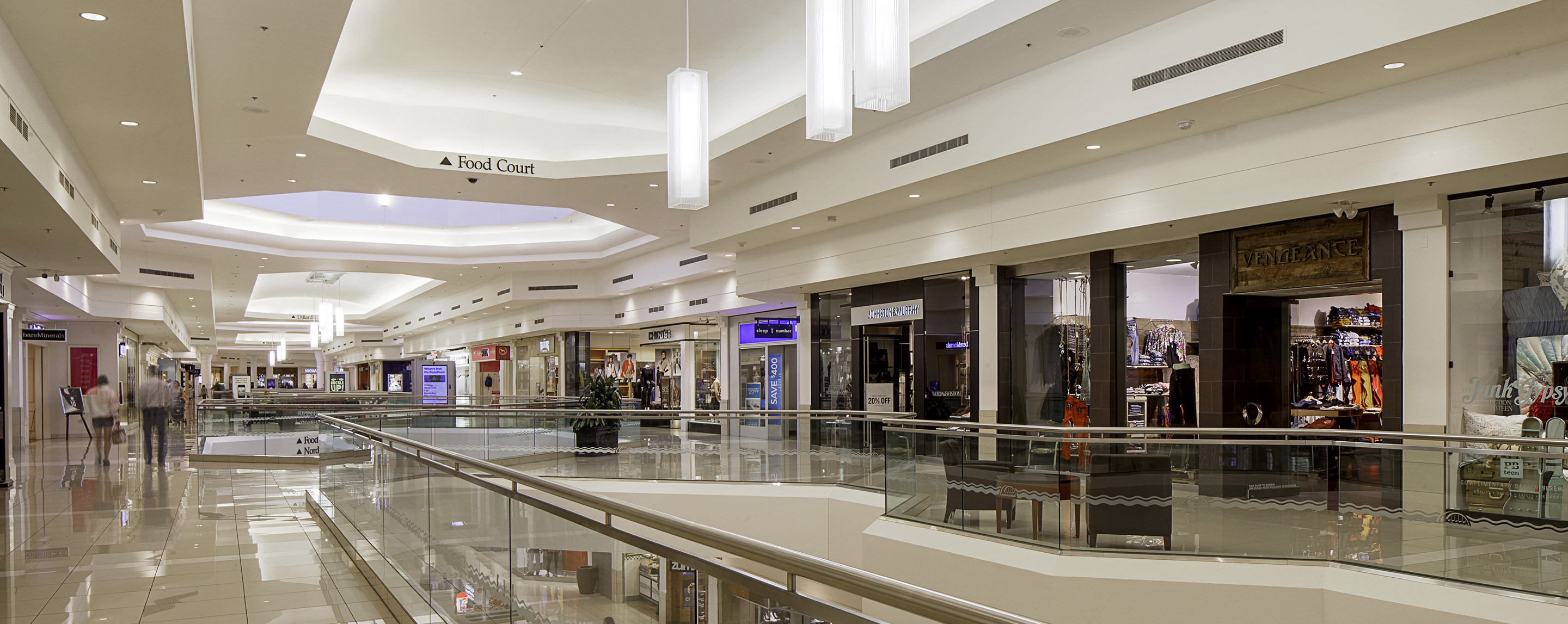In an upper level interior walkway at Kenwood Town Center, store fronts line the hallways as a few shoppers walk by.
