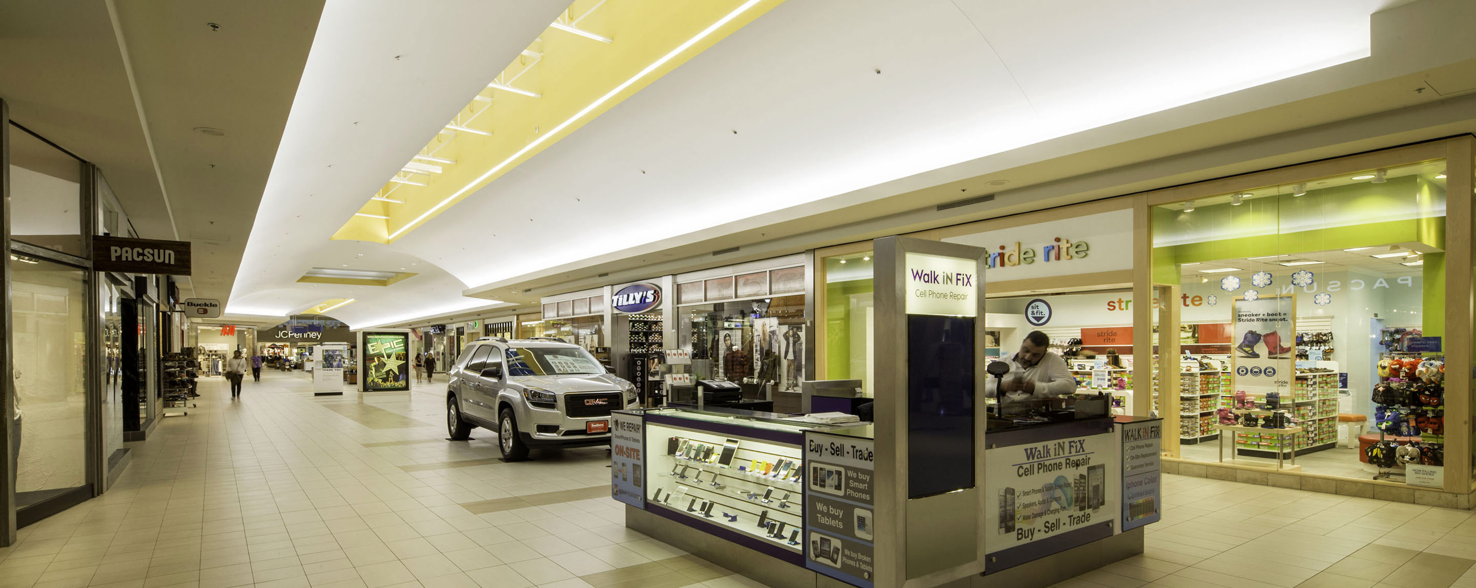 In an interior Lynnhaven Mall walkway, store fronts line the hallway and kiosks and a new car are displayed in the middle.