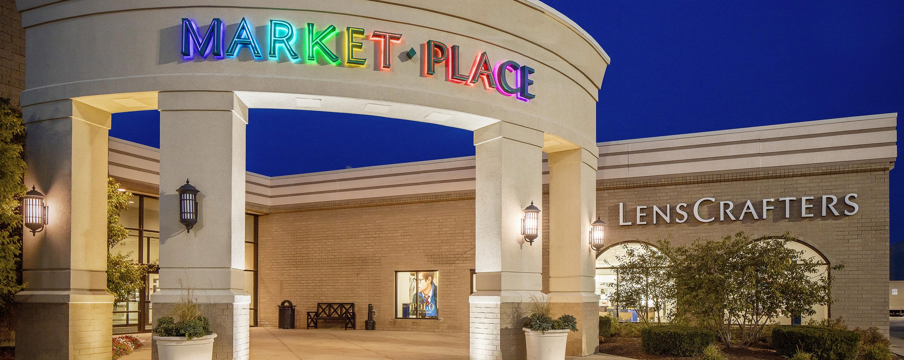 A colorful Market Place sign is lit up and is displayed on the outside entrance of the building.