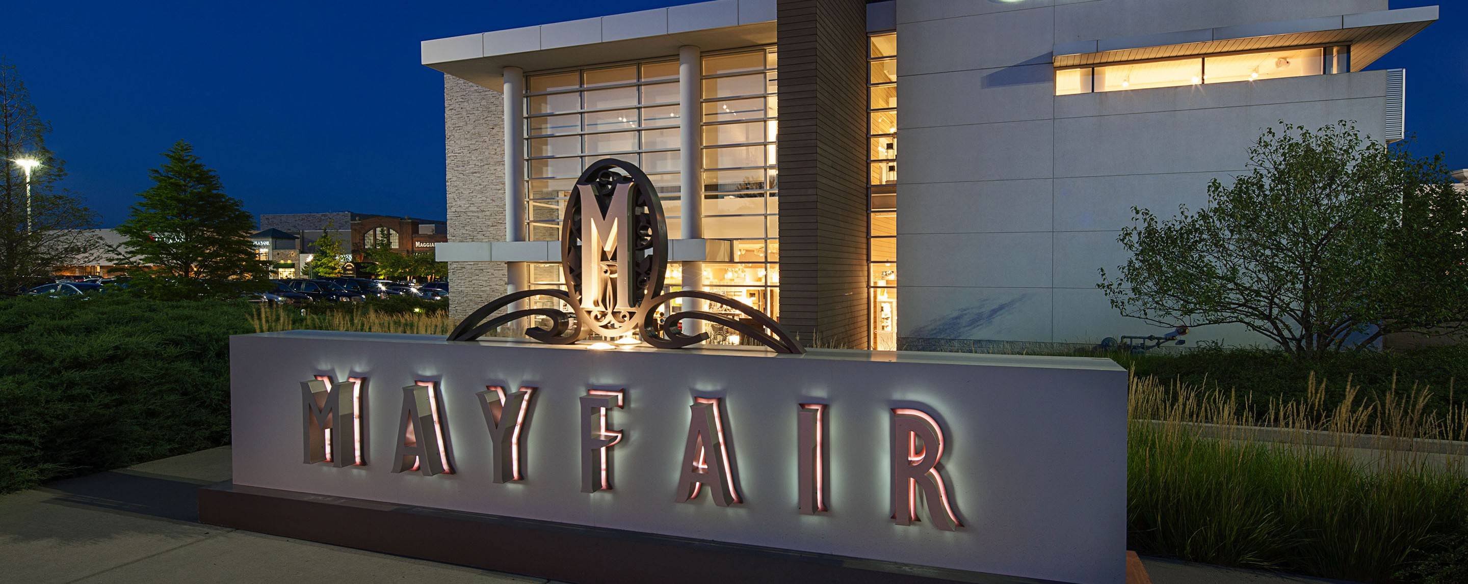 At night, the Mayfair property sign is lit up in the entrance of the property surrounded by greenery.