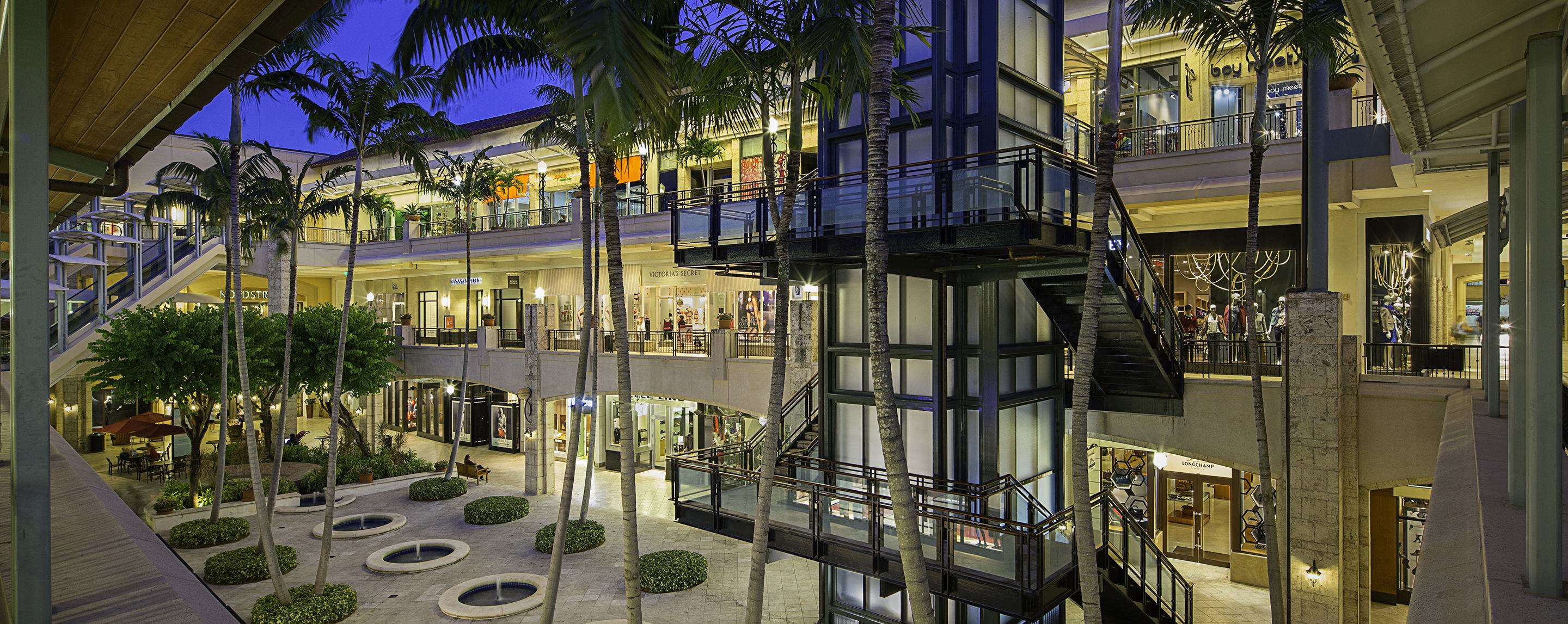In an outdoor courtyard at Shops at Merrick Park, palm trees and an elevator with attached stairs are surrounded by three levels of stores.