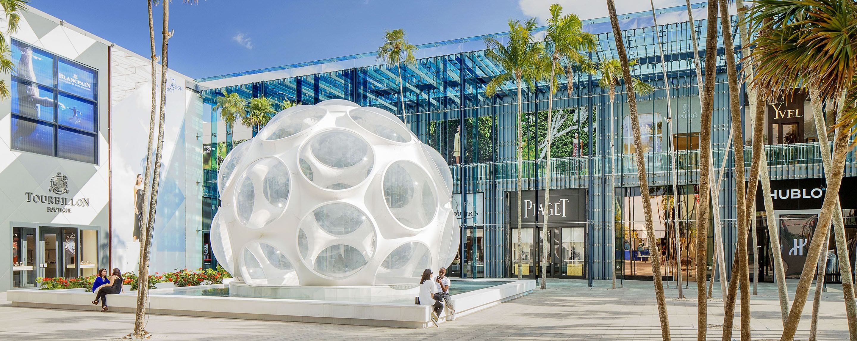 Outside a common area of the Miami Design District on a dunny day, palm tree line a sitting area with a decorative fountain.