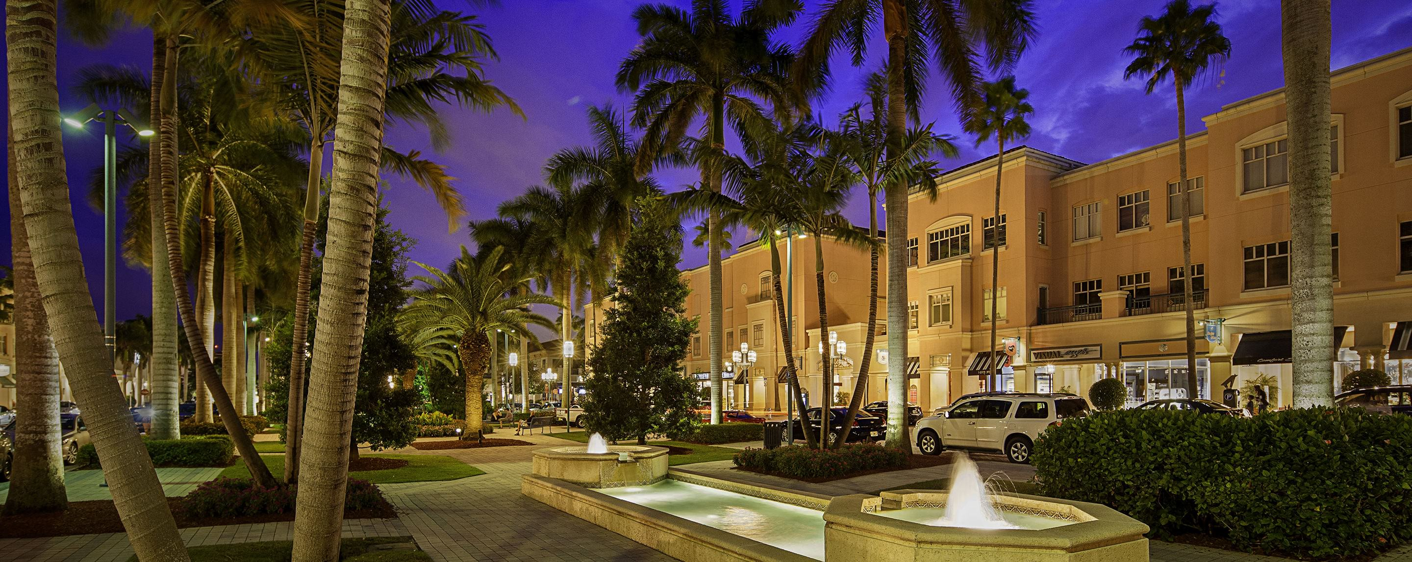 At night, palm trees and a decorative fountain can be seen in front of the Minzer Park exterior storefronts.