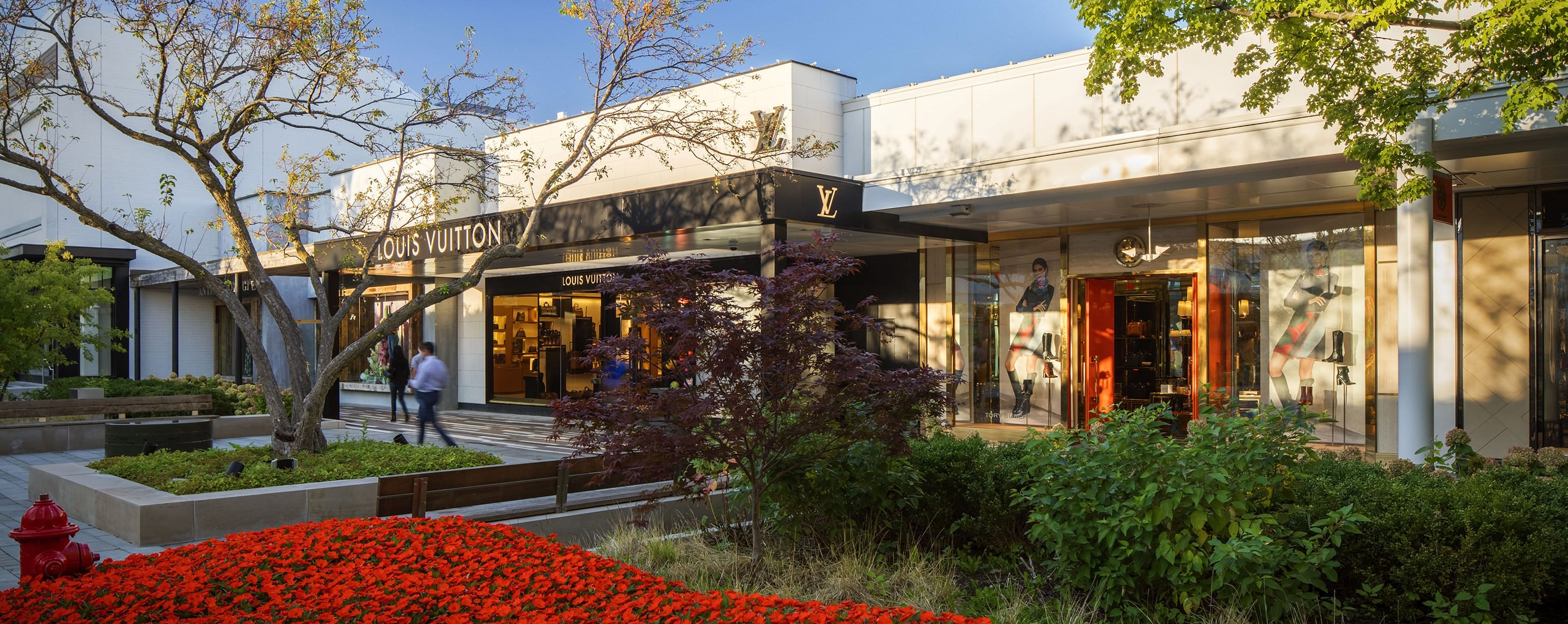 At dusk, Oakbrook Center shoppers stroll along an outdoor walkway lined with storefronts, flowers, and trees