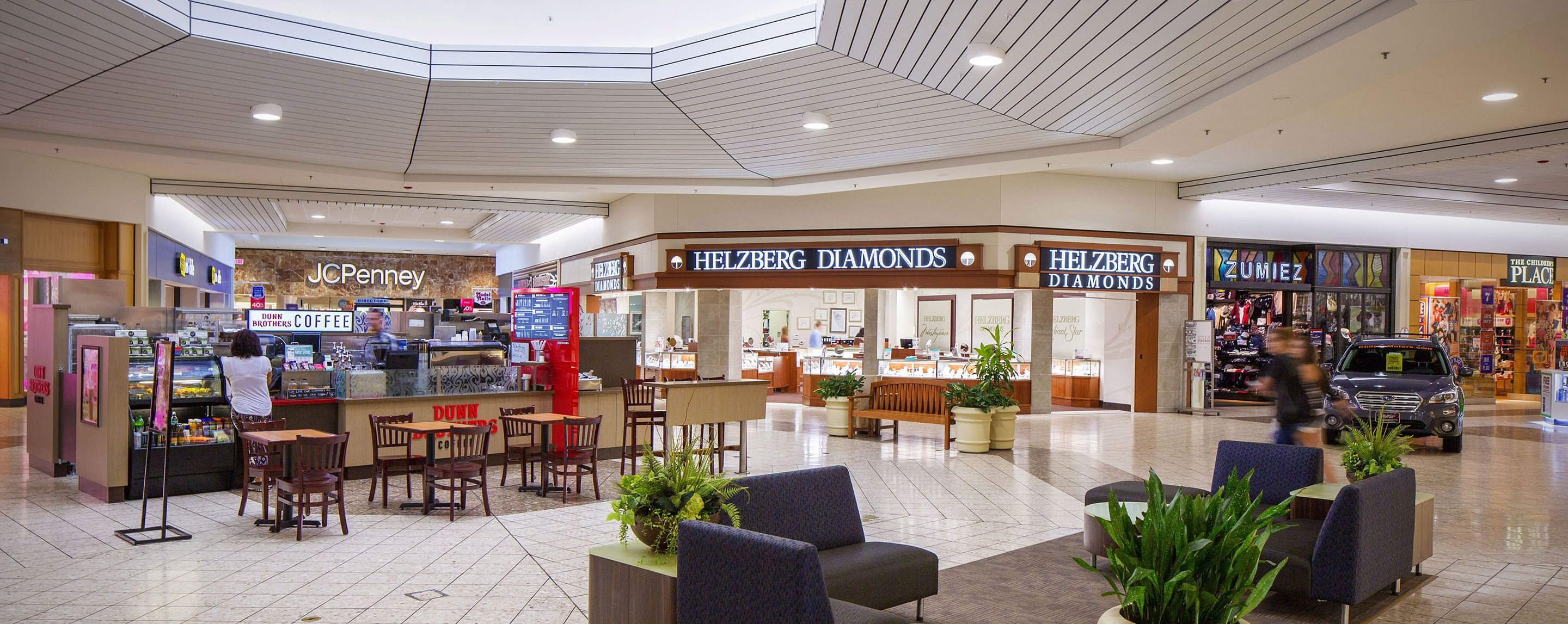In a OakWood Mall indoor common area, a coffee kiosk offers a seating area for shoppers to relax.