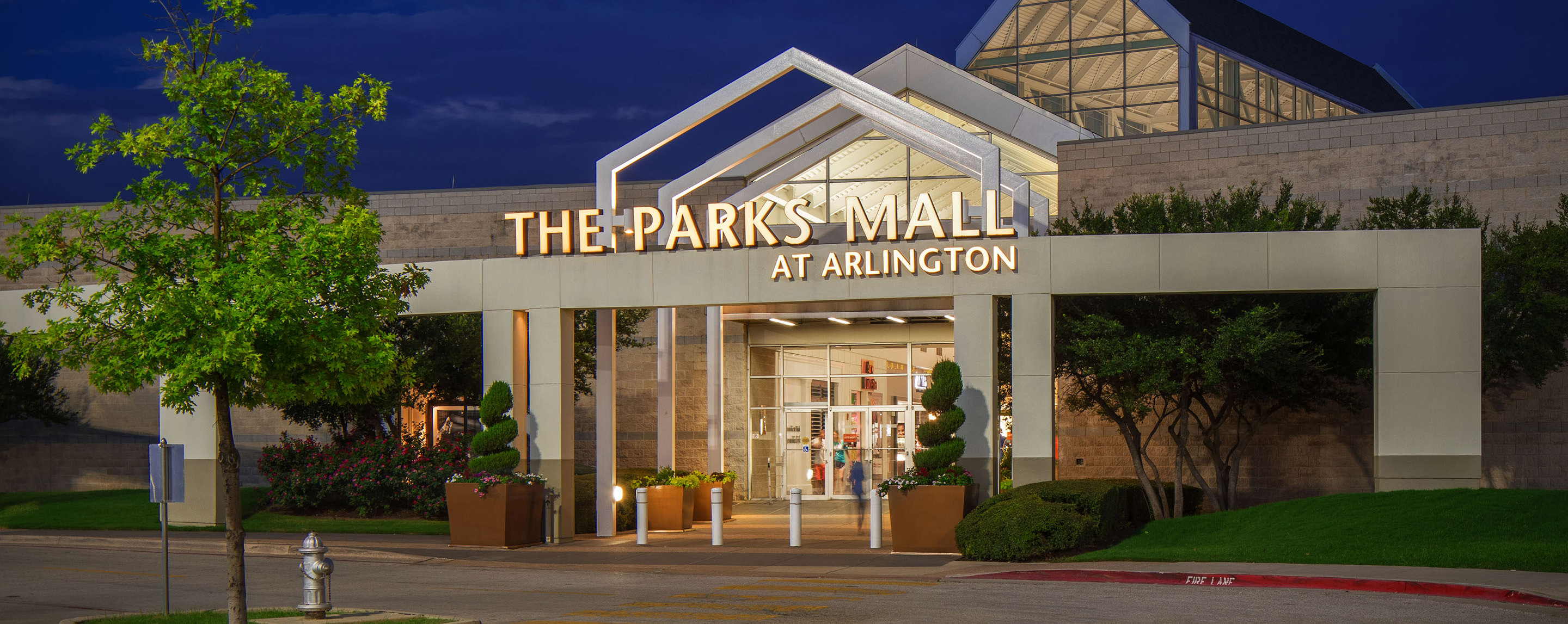 The entranceway to The Parks Mall at Arlington is brightly lit at dusk.