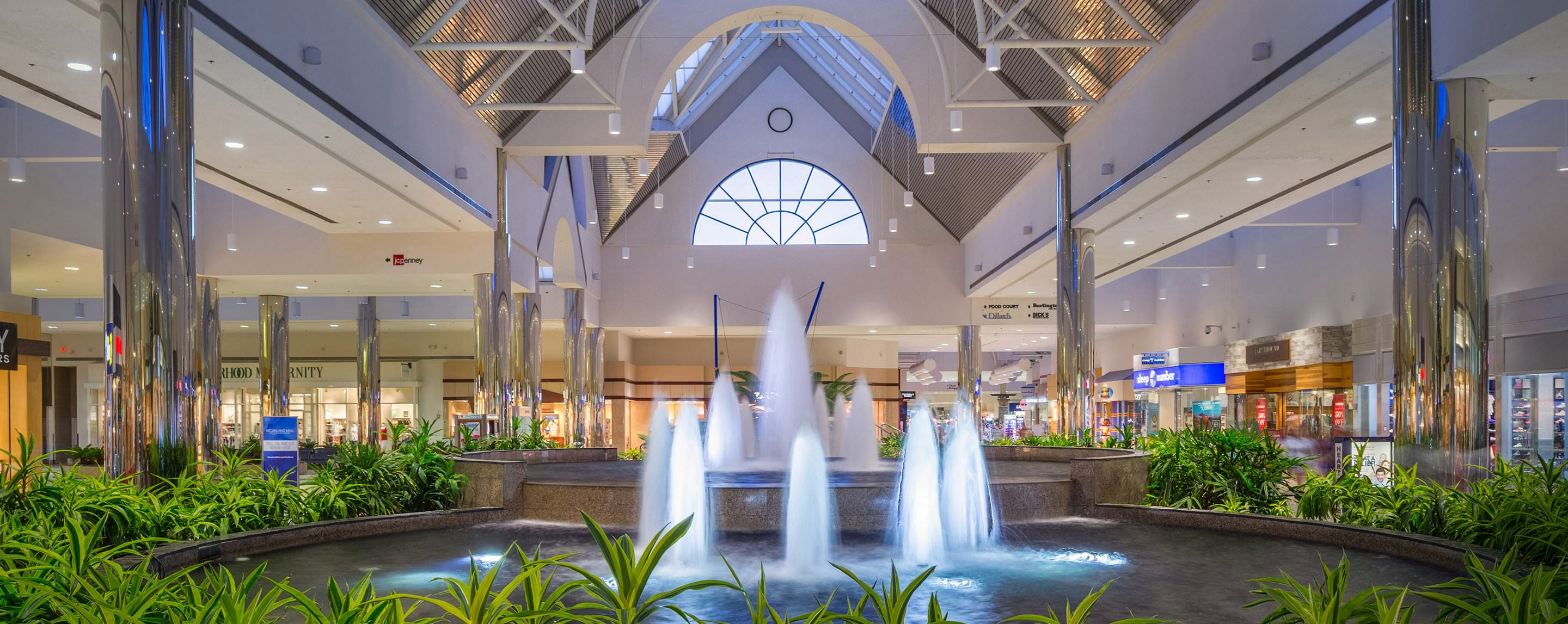 Inside of Pecanland Mall's atrium, a running fountain surrounded by plants is centered in the atrium.