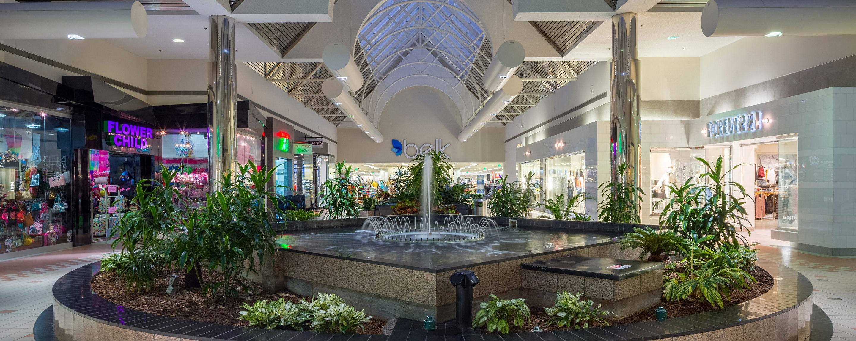 In A Common Area Of Pecanland Mall Running Fountain With Plants Is Surrounded By