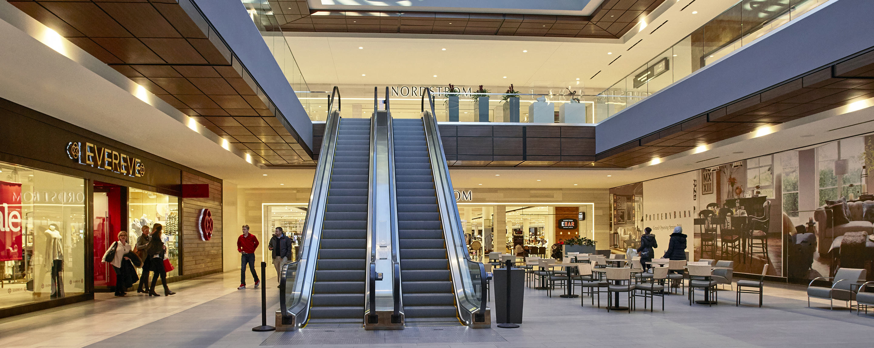Shoppers walk by the escalators and the interior entrance to Nordstrom on the top level of Ridgedale Center.