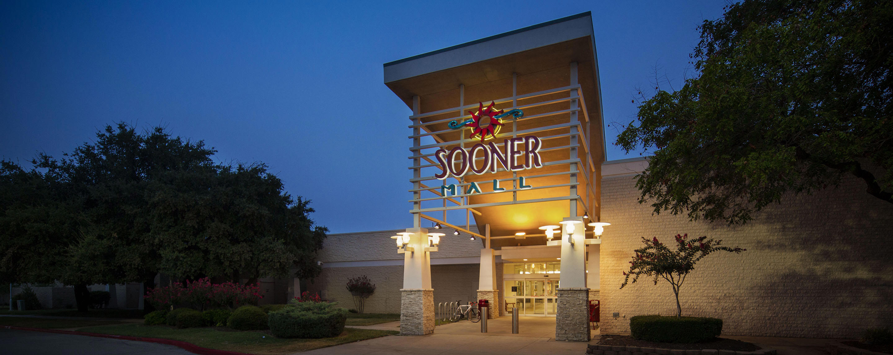 The Sooner Mall sign at an exterior entrance is lit up at dusk.