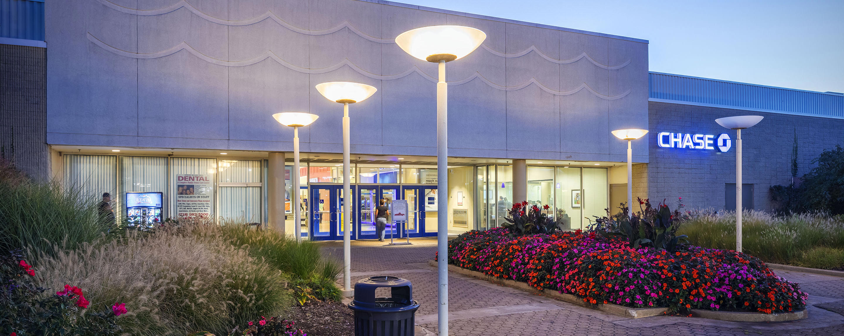 The entrance to Staten Island Mall welcomes shoppers with beautiful flowers and greenery at dusk.