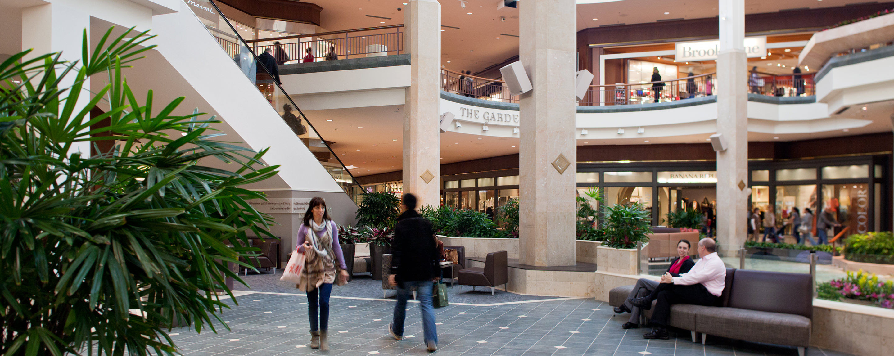Stores and a plan are visible as shoppers walk across the common area on the lower level of Saint Louis Galleria.
