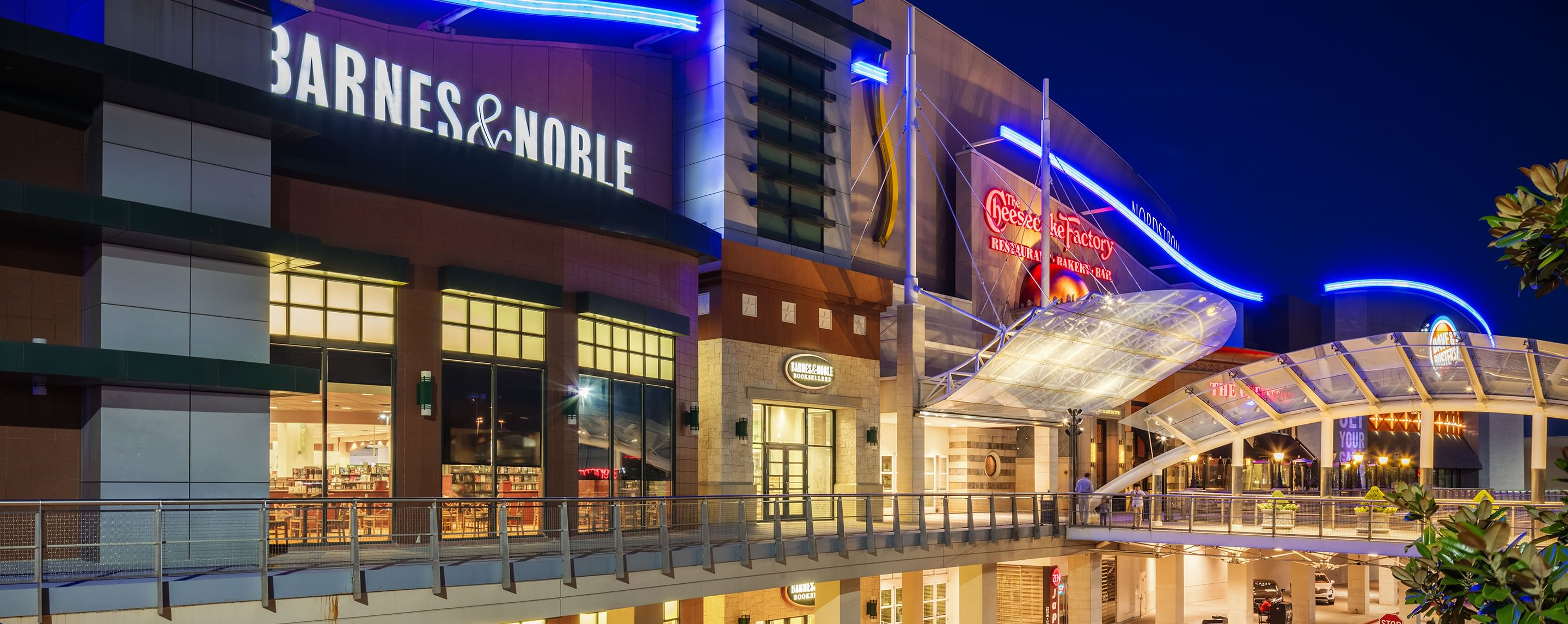 At dusk, stores such as Barnes & Noble and The Cheesecake Factory are alight at Stonebriar Centre.