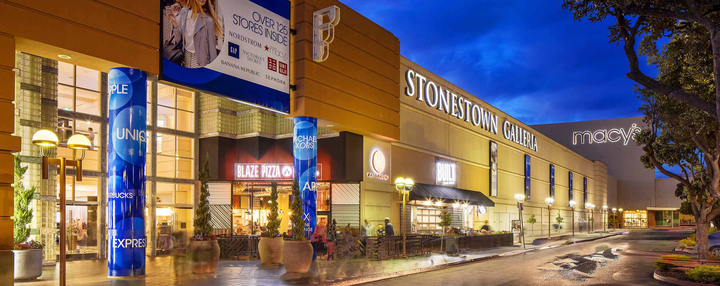 The exterior entrances of Stonestown Galleria is brightly lit at night.