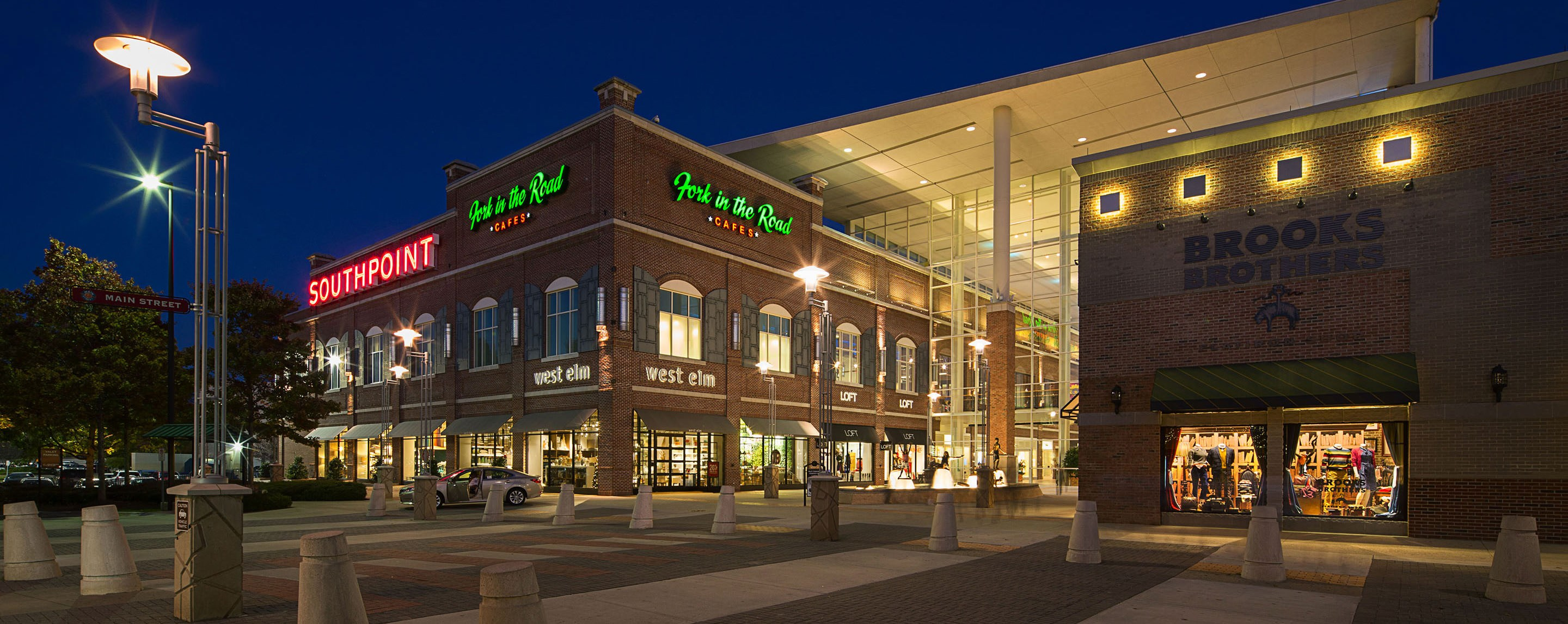 The Streets at Southpoint is seen from outside at night illuminated by interior lighting and storefronts.