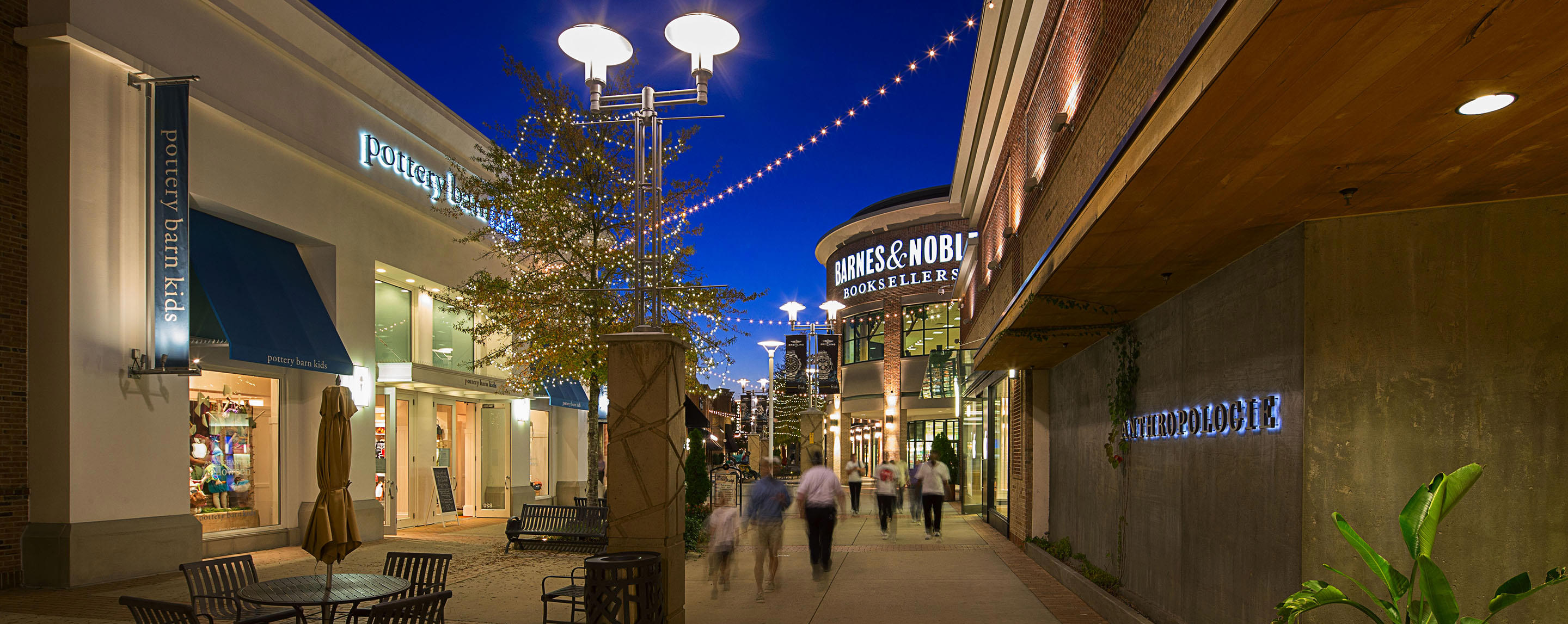 Shoppers stroll along the exterior walkway illuminated by decorative string lights, storefronts and outdoor lamps.
