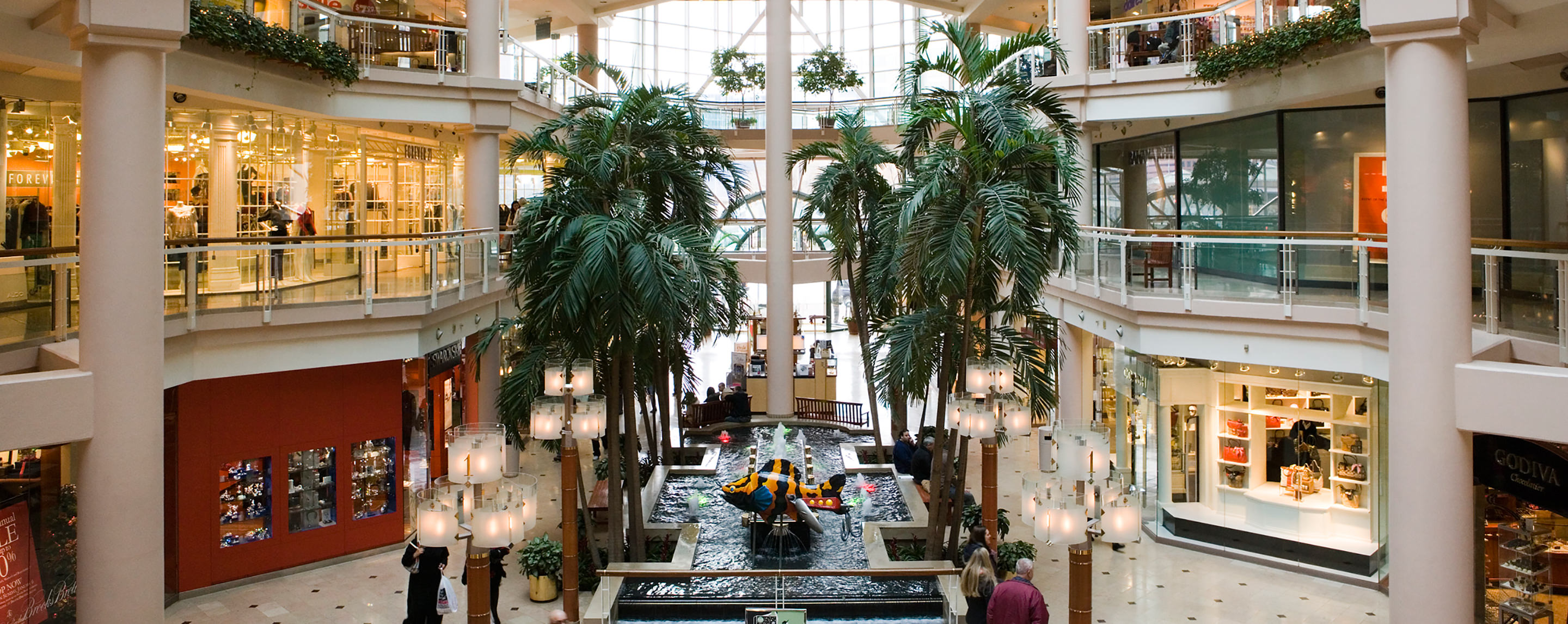 Decorative landscaping adorns a common area between several levels of retailers at The Gallery at Harborplace.