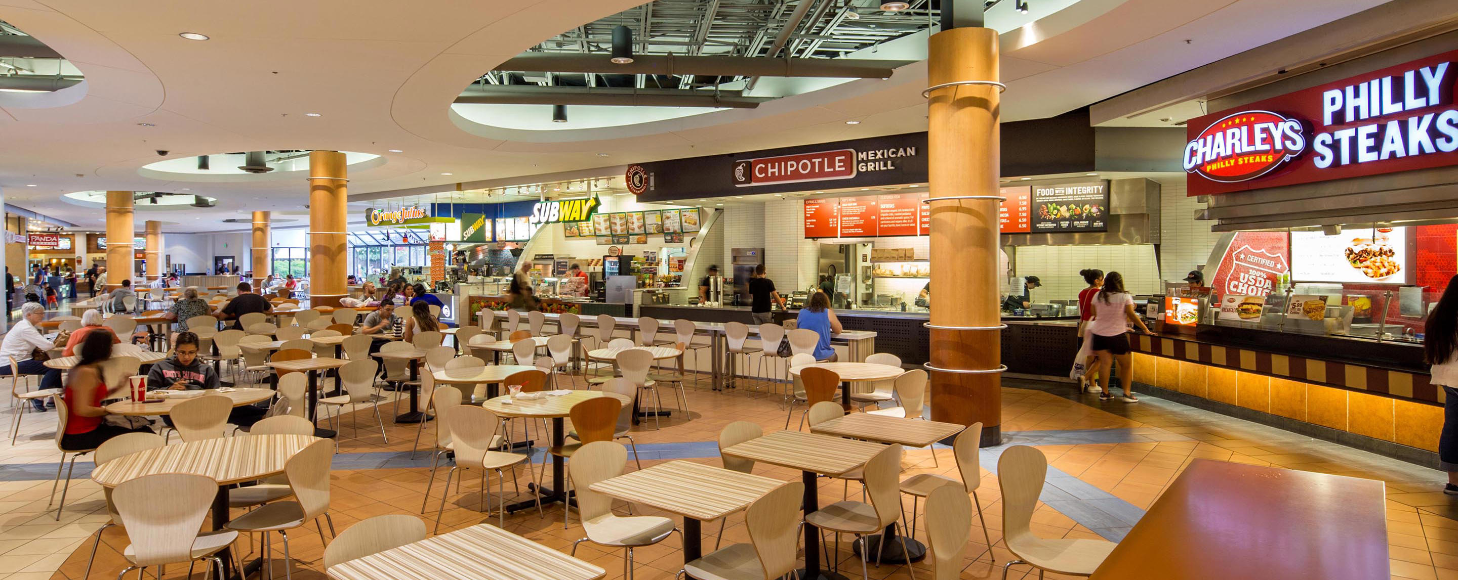 Tucson Mall's food court is set up with various tables and chairs for shoppers to take a break and eat.